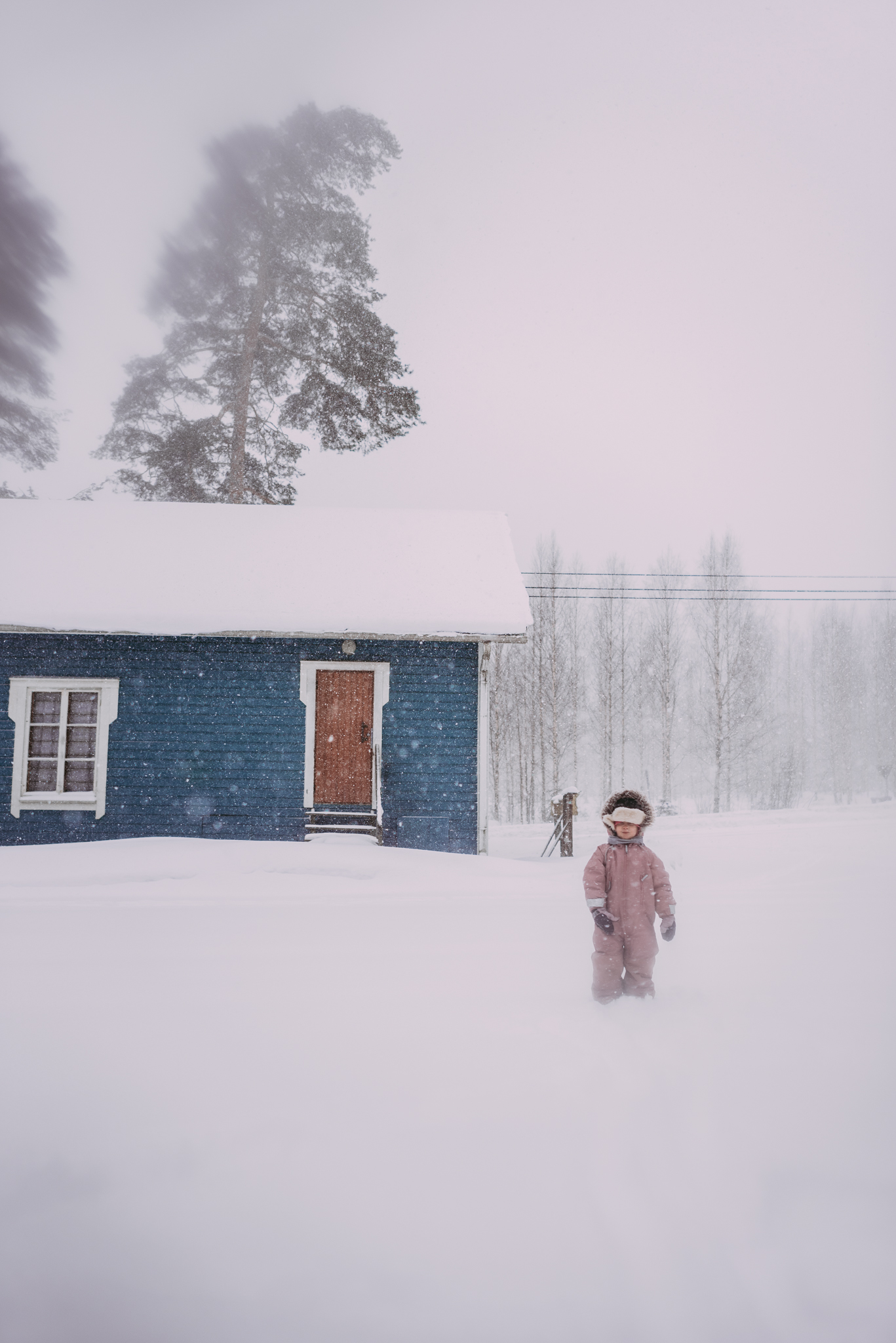 girl in front of blue house in snowstorm