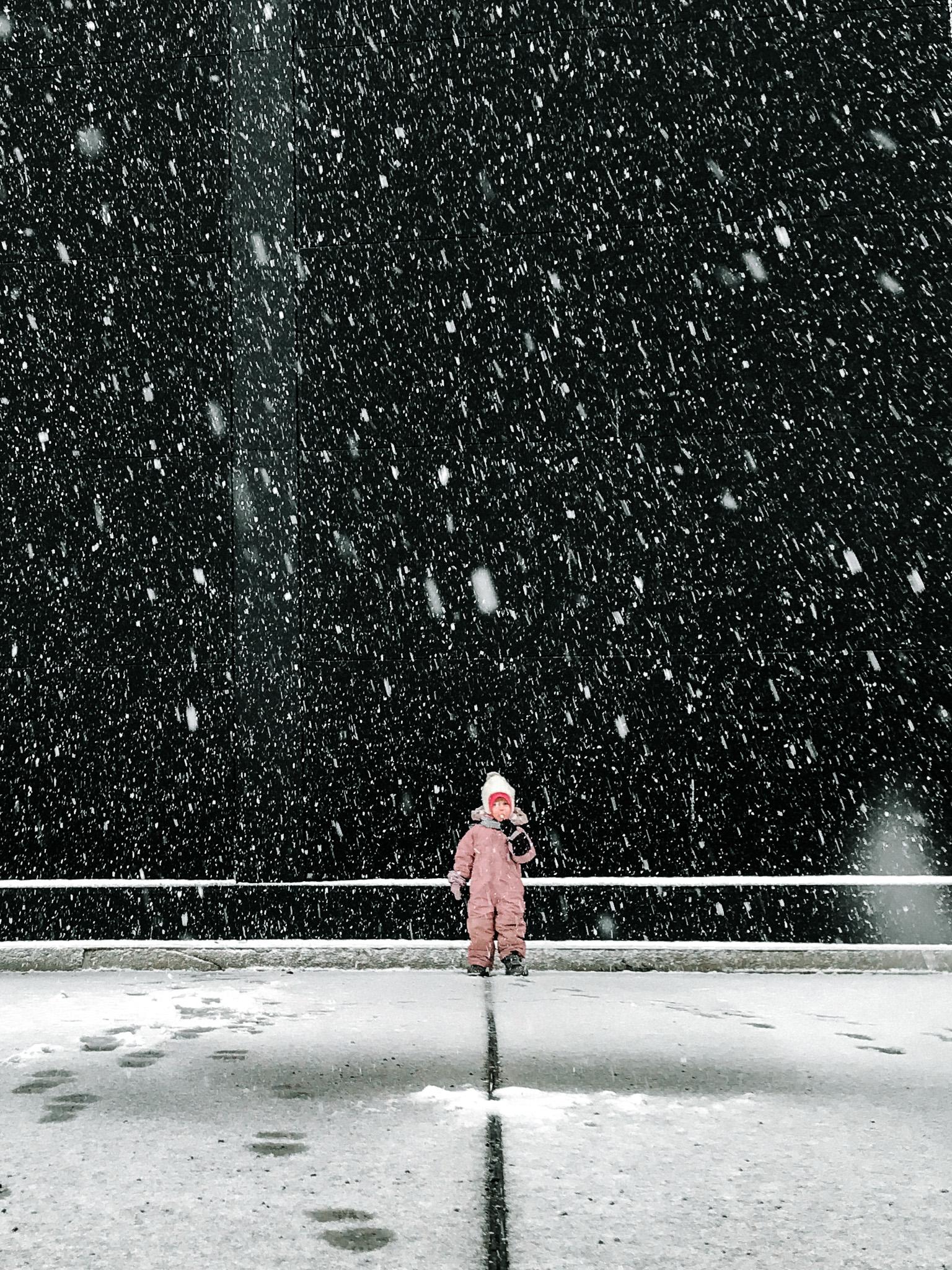 little girl in snowy parking lot