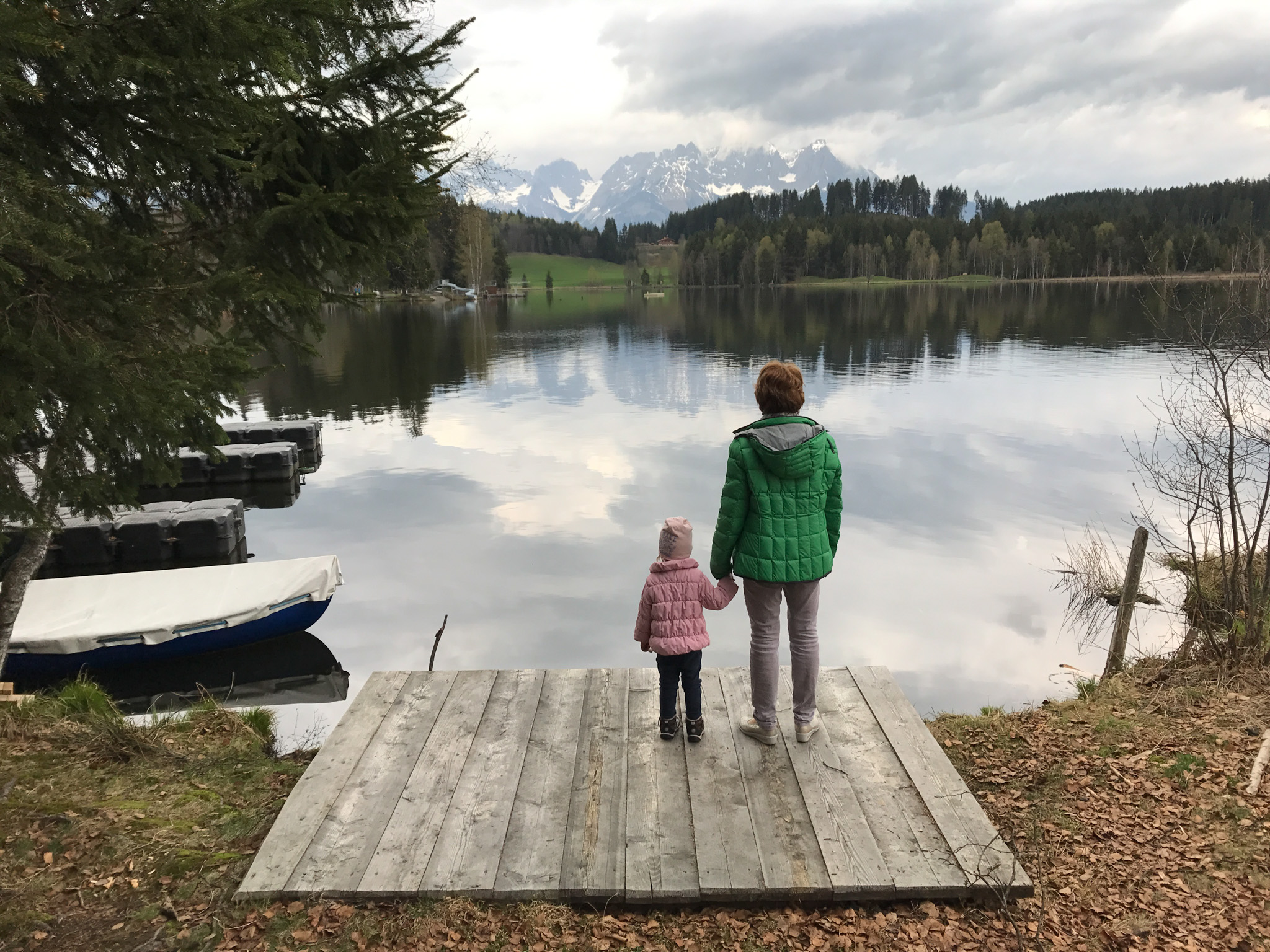 Woman and child starring at the lake where mountains reflect
