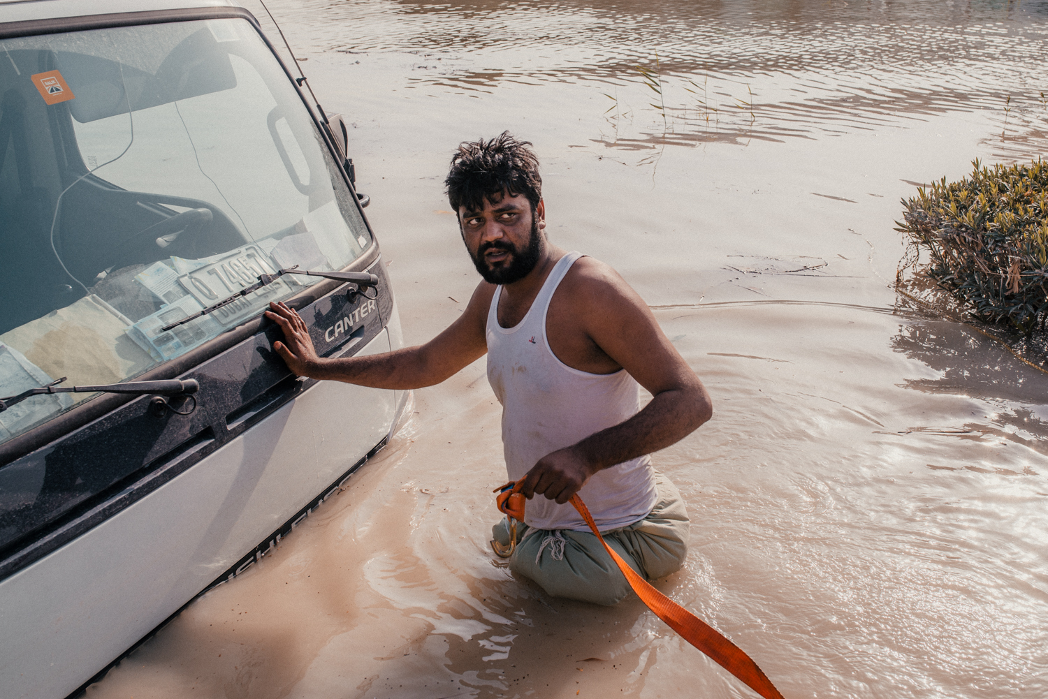 A man attempts to rescue his truck after heavy downpours flooded the street it was parked on in Dubai.