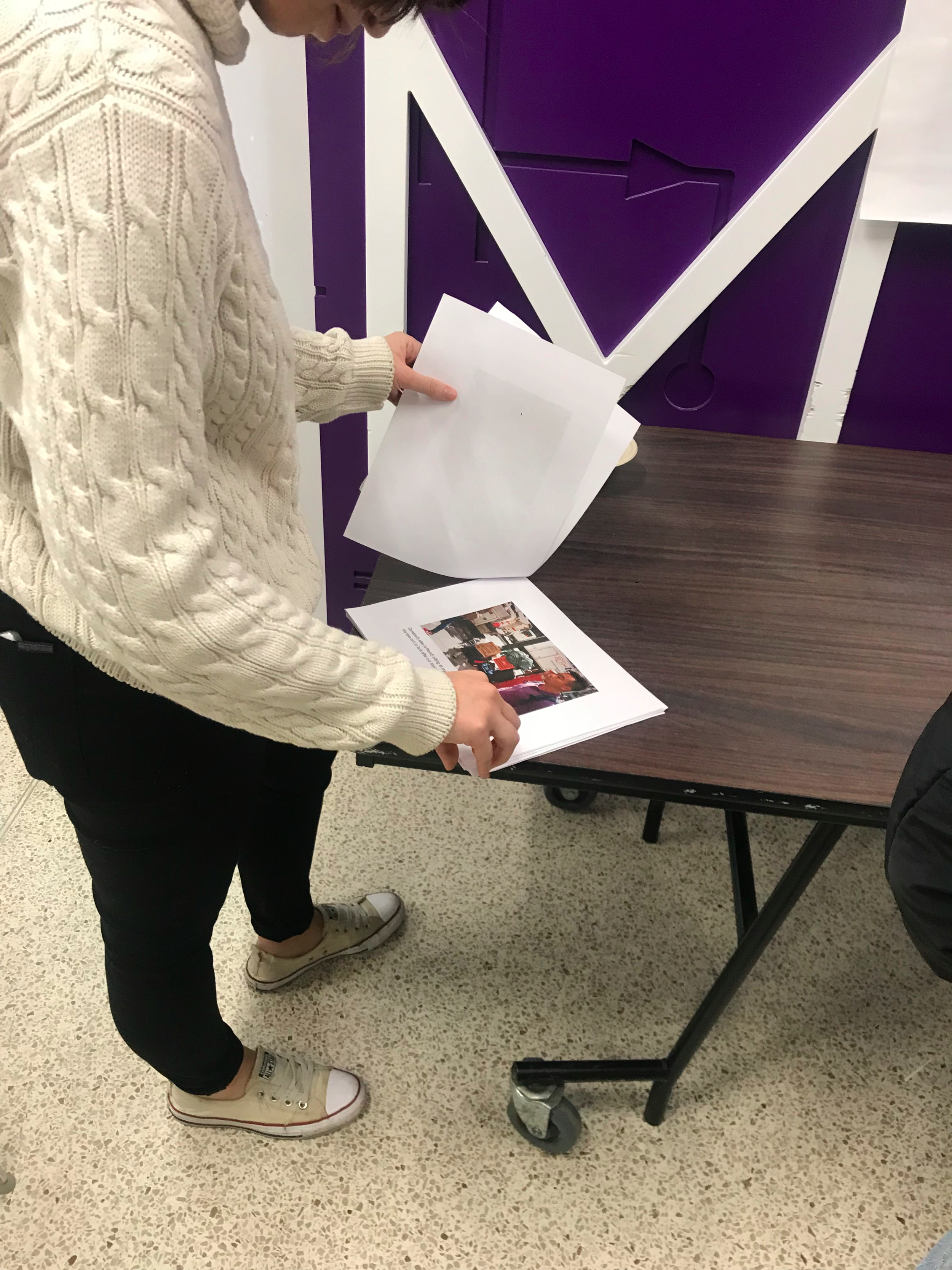 Student_looking_at_photo_book_by_Tabby_homelesswoman1_biographical.png