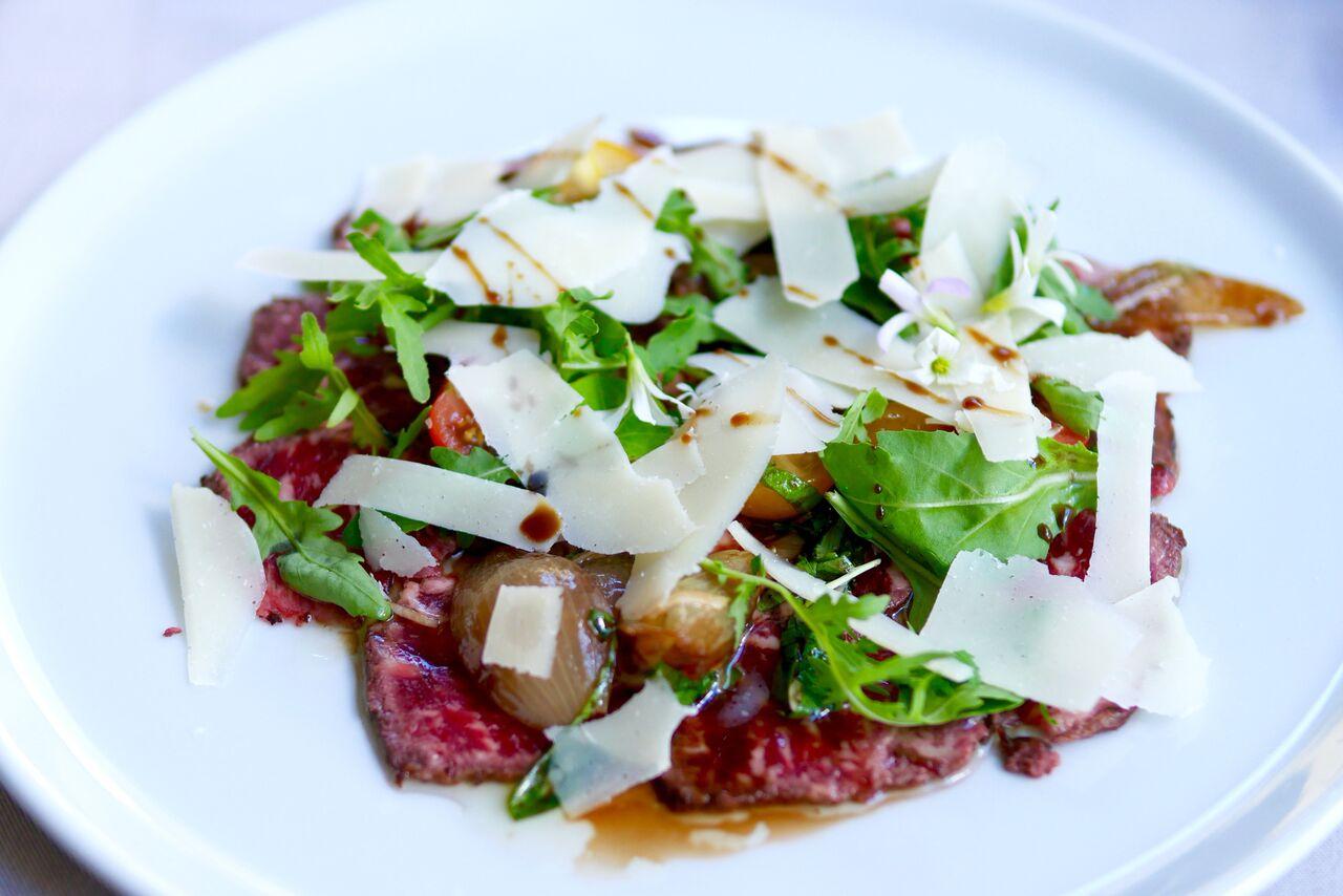 VEISELIHA CARPACCIO 11€   Rucola, pähklid, tomatisalsa, sibul, parmigiano juust   Veiseliha carpaccio on miski, mida kohtab pea igas restoranis ja üsna samasugusel kujul. Siin aga selgus peakokaga vesteldes, et liha on just spetsiaalselt tavalisest paksemaks jäetud, et tuua rohkem esile selle maitset. Ja see magus karamelline sibul oli ikka tõeline primadonna, tegemist on tõesti oskuslikult valitud lisandiga - meeletult hea. Meile selline alternatiivne carpaccio väga meeldis, liha maitse tuli paremini esile kui klassikalise, eriti õhukese carpaccio puhul, kus vaat, et neelad tüki liha alla enne, kui maitset tunned. SOOVITAME!