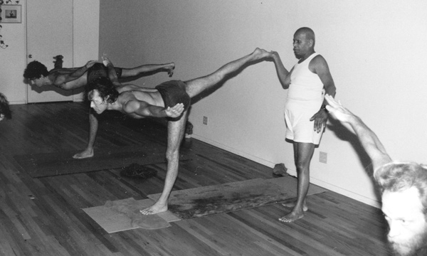 Pattabhi Jois adjust students during practice.