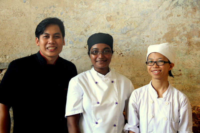 """ The kitchen team at The Granary is headed by Head Chef Lutonia Naicker (center) together with her Sous Chef Marthineus Langi (left) and also the Pastry Chef Monica Nani (right).  Our team is a melting pot of cultures and experiences; from Sarawak, South Africa, New Zealand, America, China and Hong Kong. We all come from different backgrounds and  ambitions, Lutonia would like to impact underprivileged youth through her love of food,  Martin aims to put Bornean cuisine on the map and Monica just loves all things baking  and genuinely enjoys creating sweet treats! Together they hope to share their passions  and make their mark on Sarawak!"""