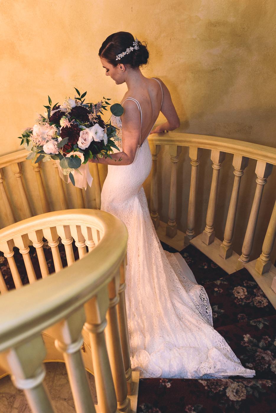 Elegant bride descending spiral staircase with bouquet