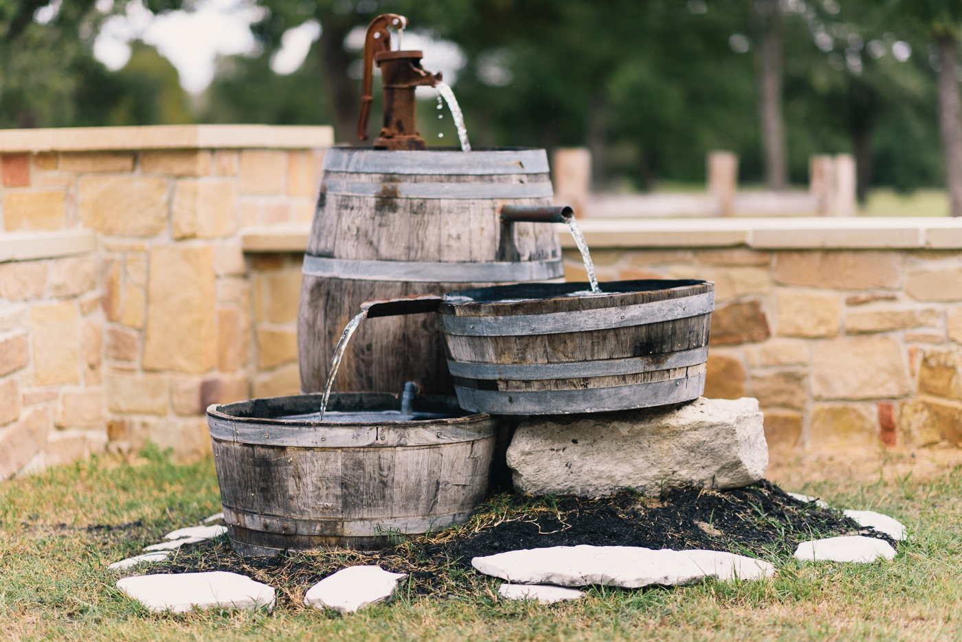Rustic barrel water fountain rock wall