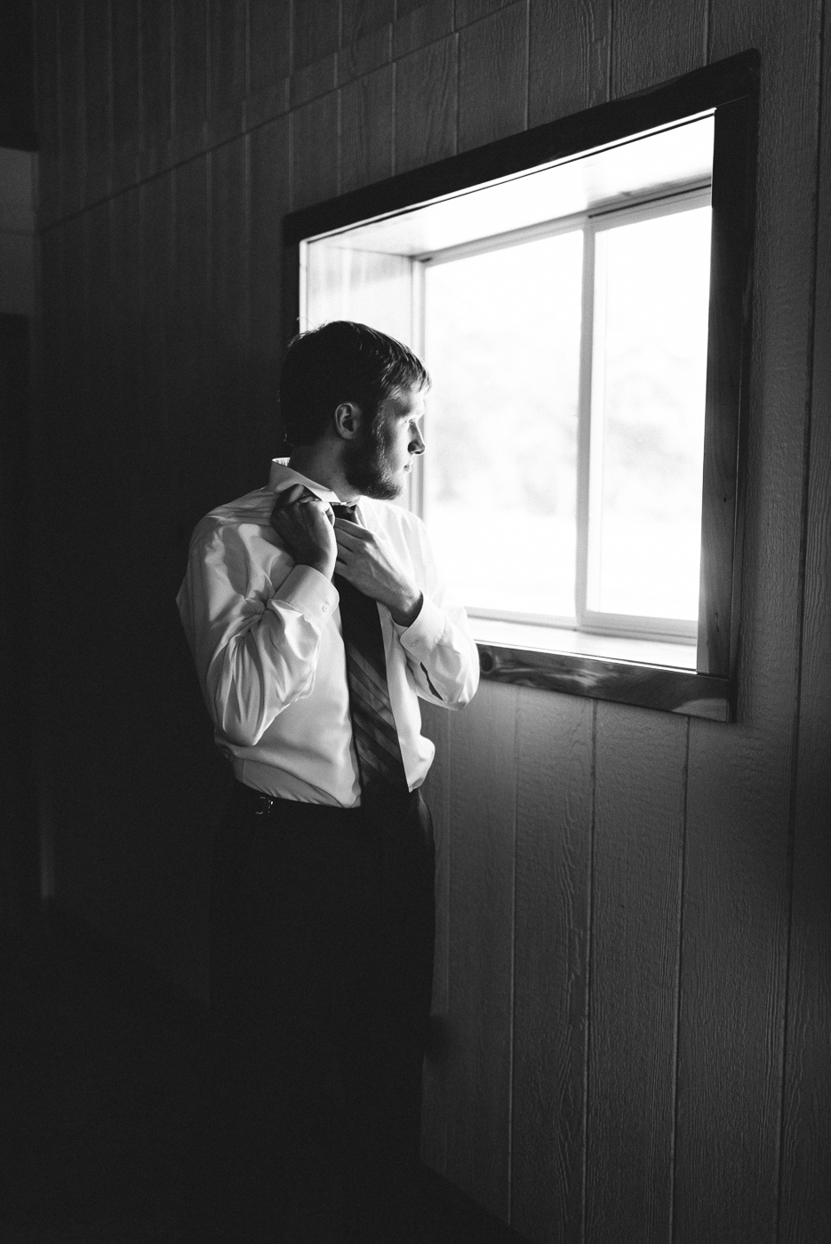 Black and white groom portrait getting ready shot tie window