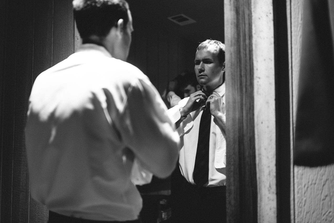 Getting ready shot groomsman tie back and white suit