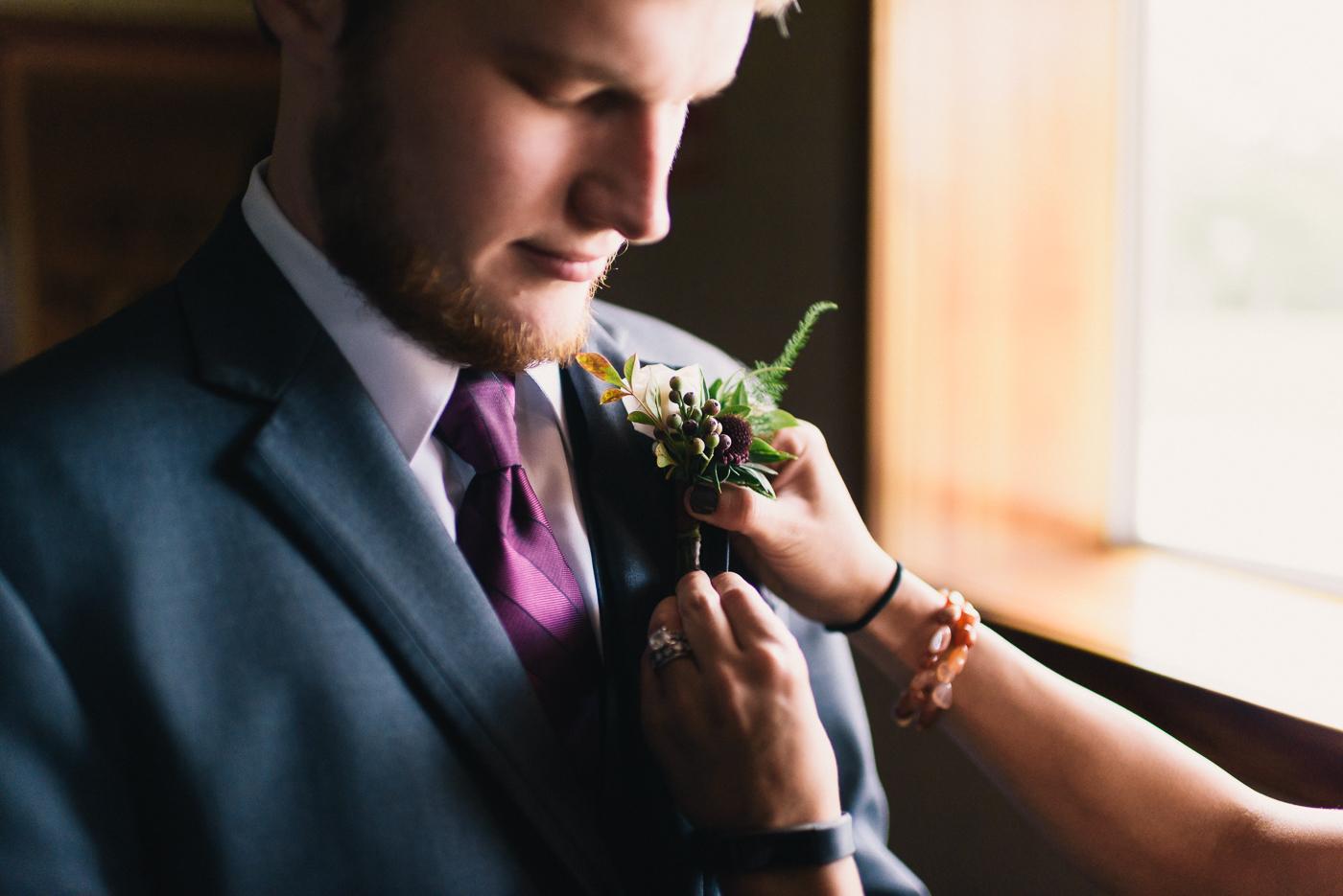 Getting ready shot groom boutonniere maroon tie