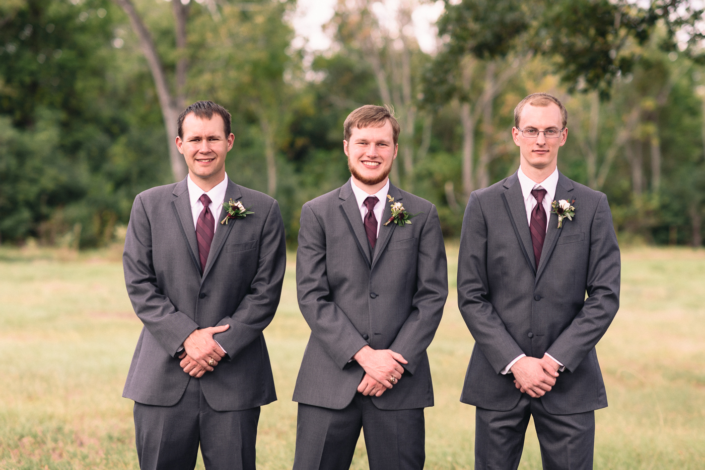 Groom and groomsmen portrait cousins boutonniere suit maroon dapper smile