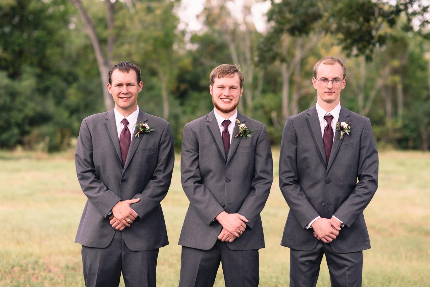 Groom and groomsmen portrait cousins boutonniere suit maroon dapper smile