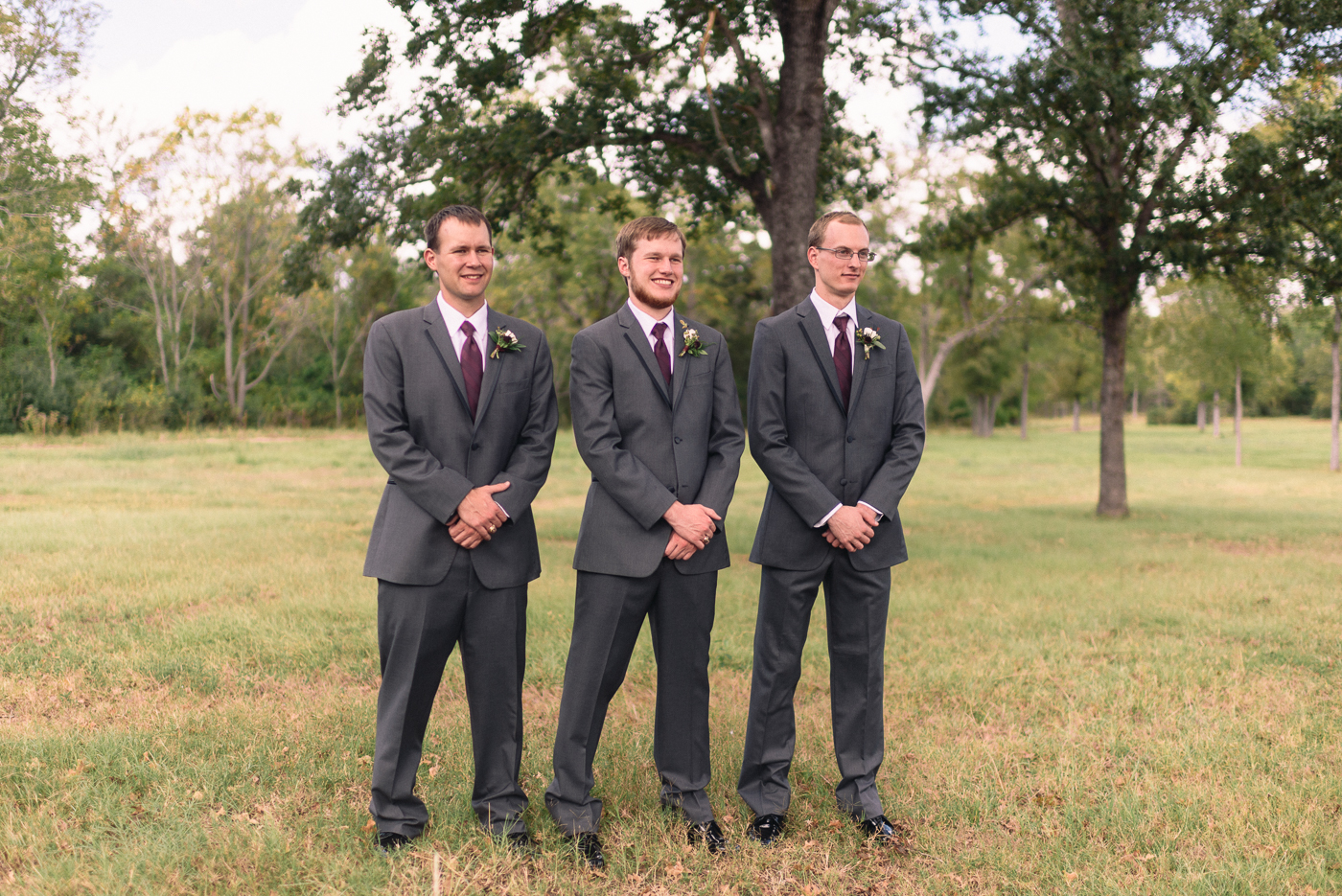 Groom and groomsmen portrait cousins boutonniere suit maroon dapper angled shot
