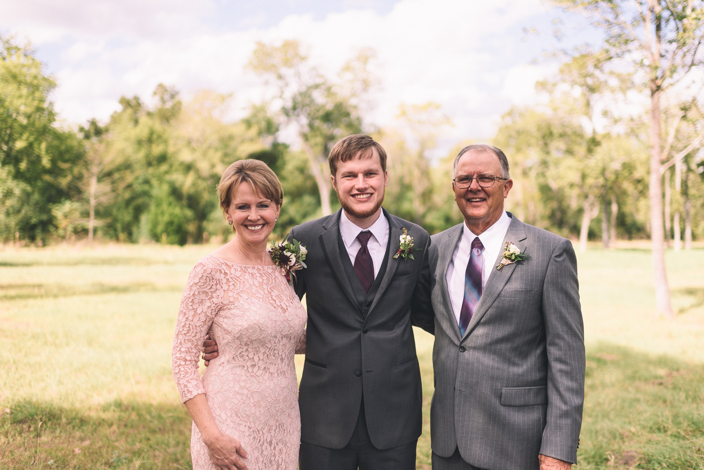 Groom's family wedding portraits mom and dad suit smile