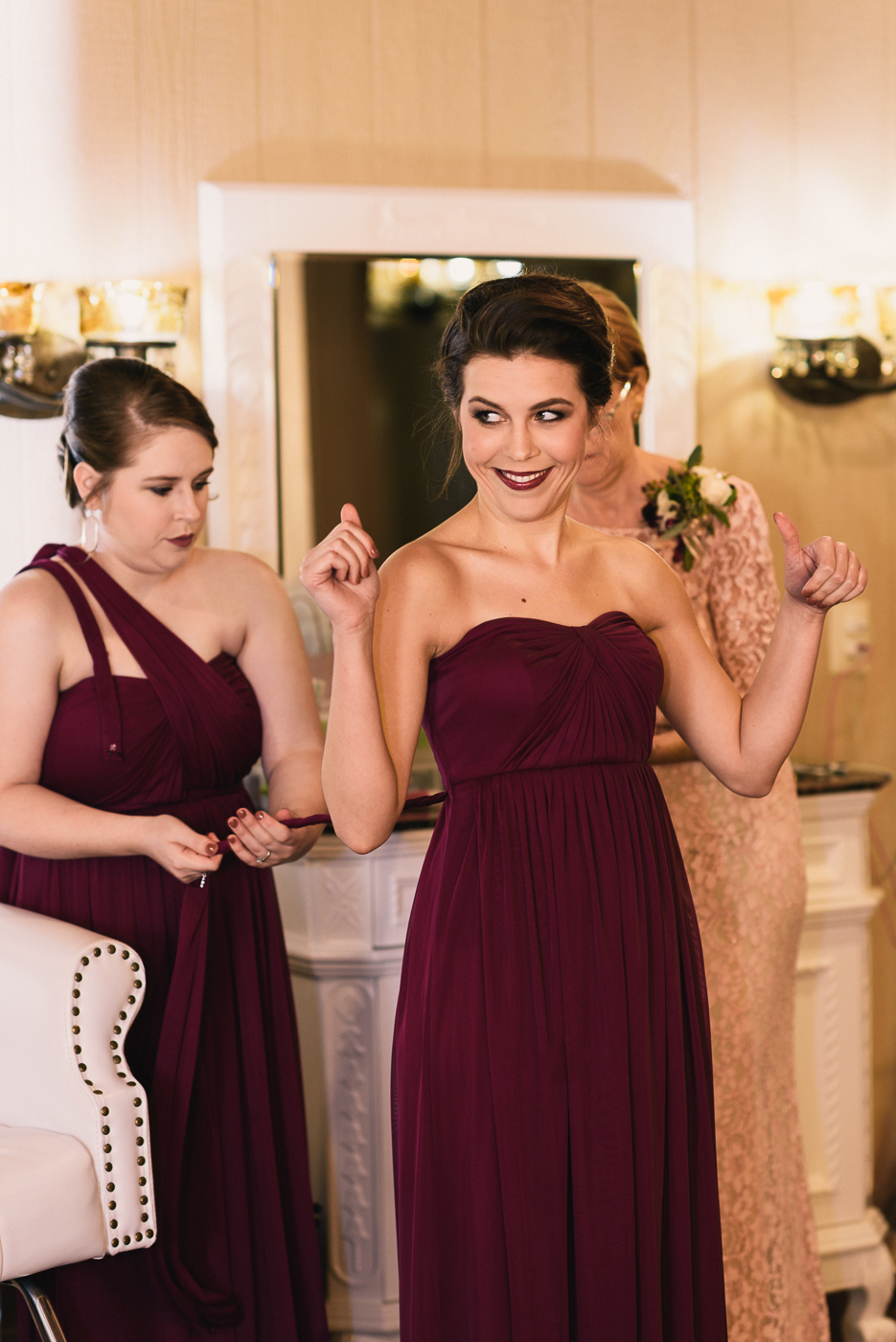 bridesmaid getting ready maroon dress hair and makeup dress tie lipstick sister of the groom