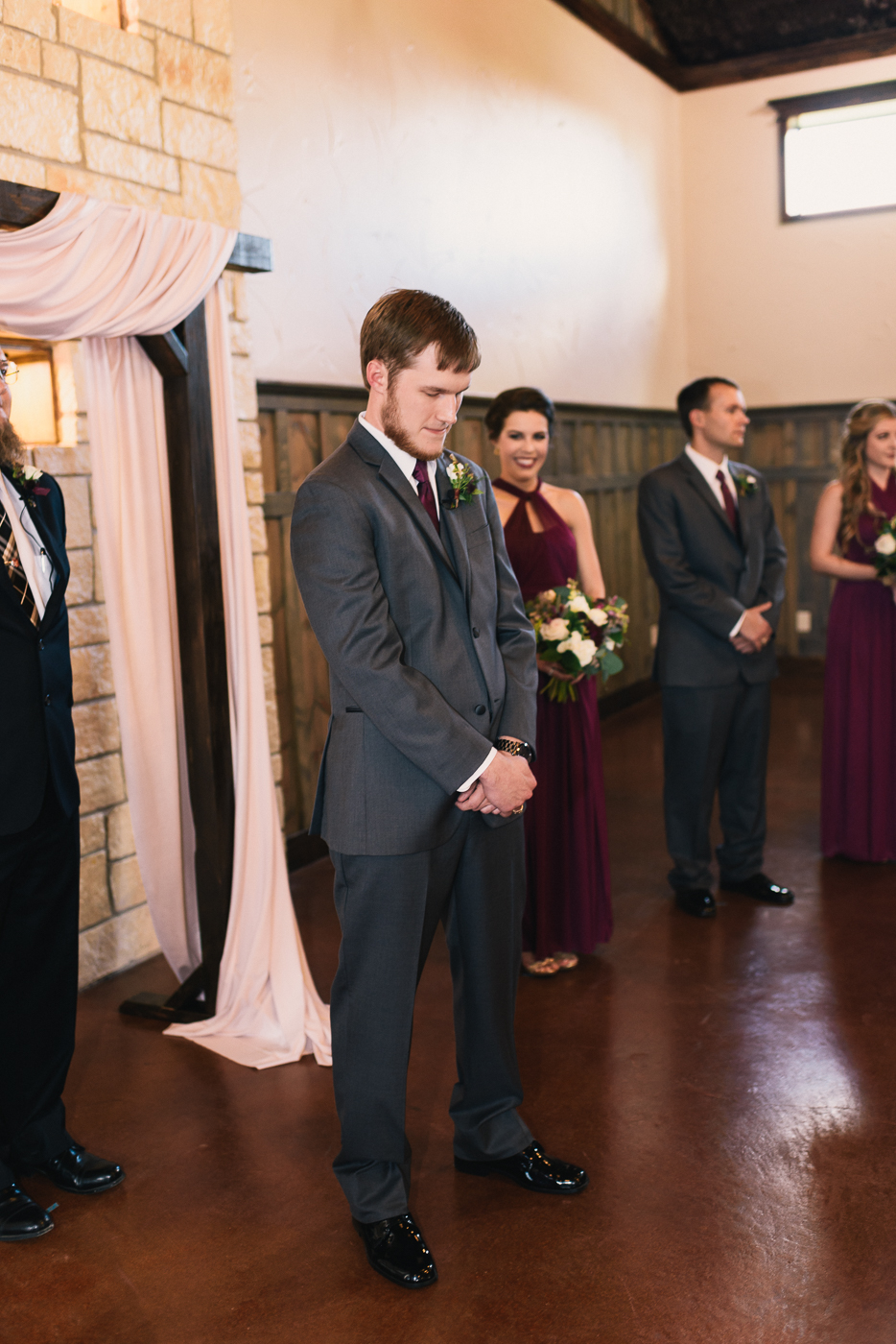 Groom at the altar wedding party dapper suit maroon wedding officiant