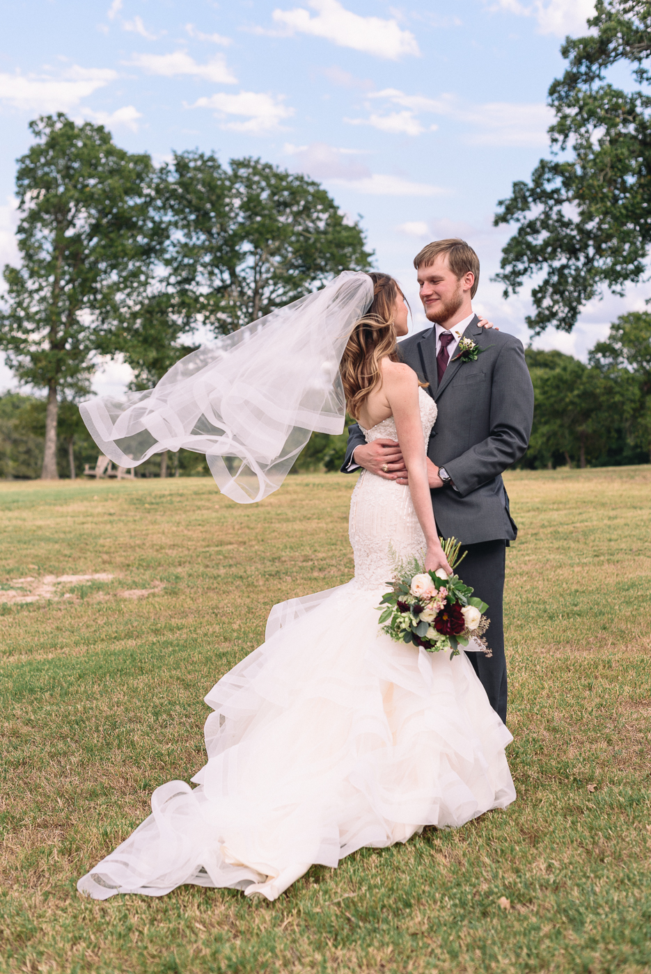 Husband and wife veil wind blue sky broken arrow ranch happy couple