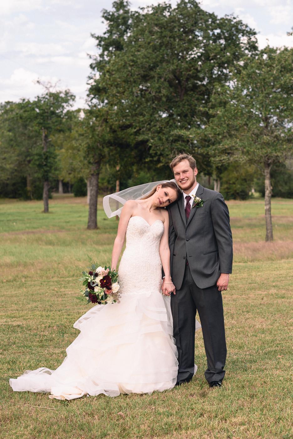 wedding portrait husband and wife holding hands broken arrow ranch maroon tie