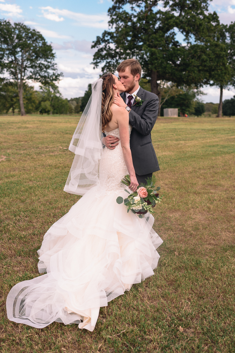 husband and wife kiss mermaid gown bouquet