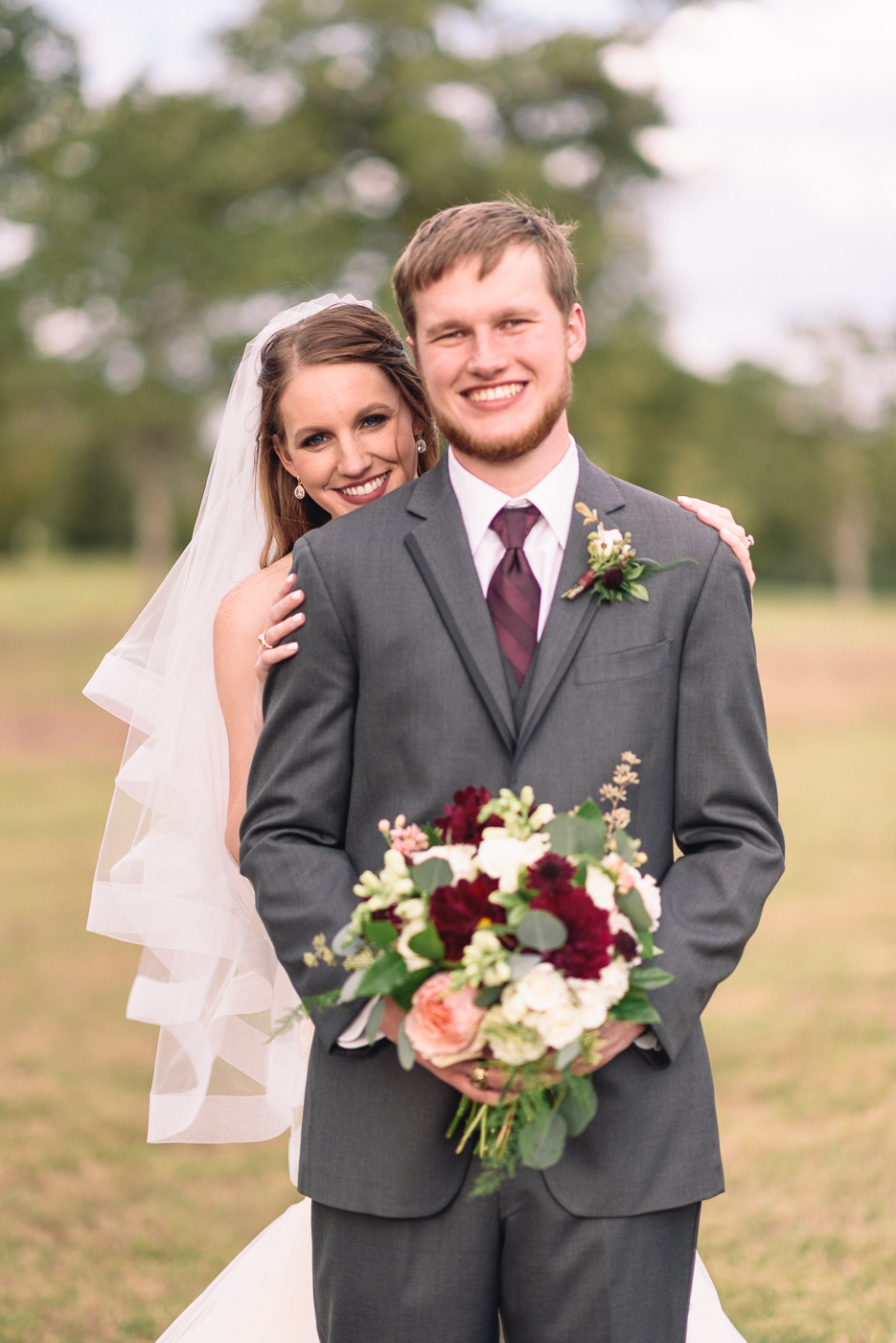 wedding portrait husband and wife maroon tie bouquet