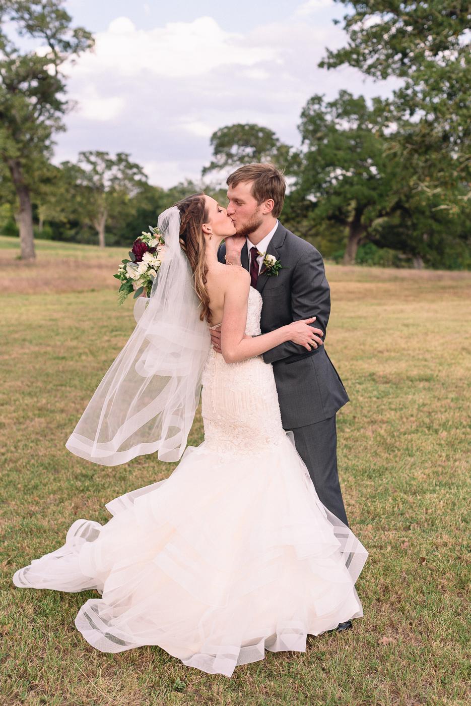 husband and wife kiss wedding portrait broken arrow ranch blue sky