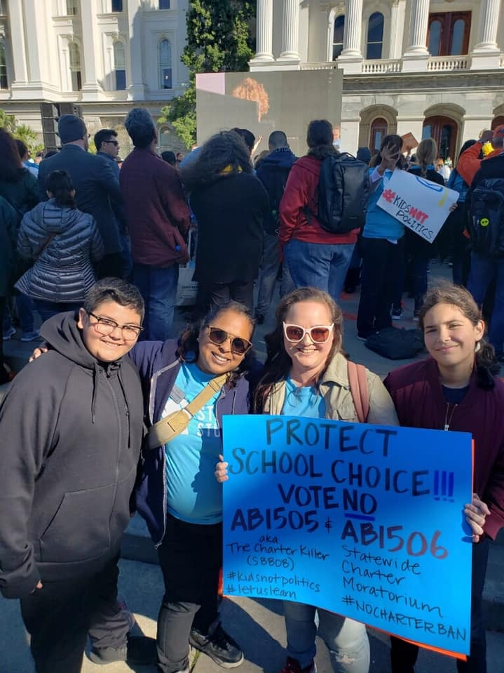 Roxann Nazario (second from right) protesting bills that could shut her daughter's school down