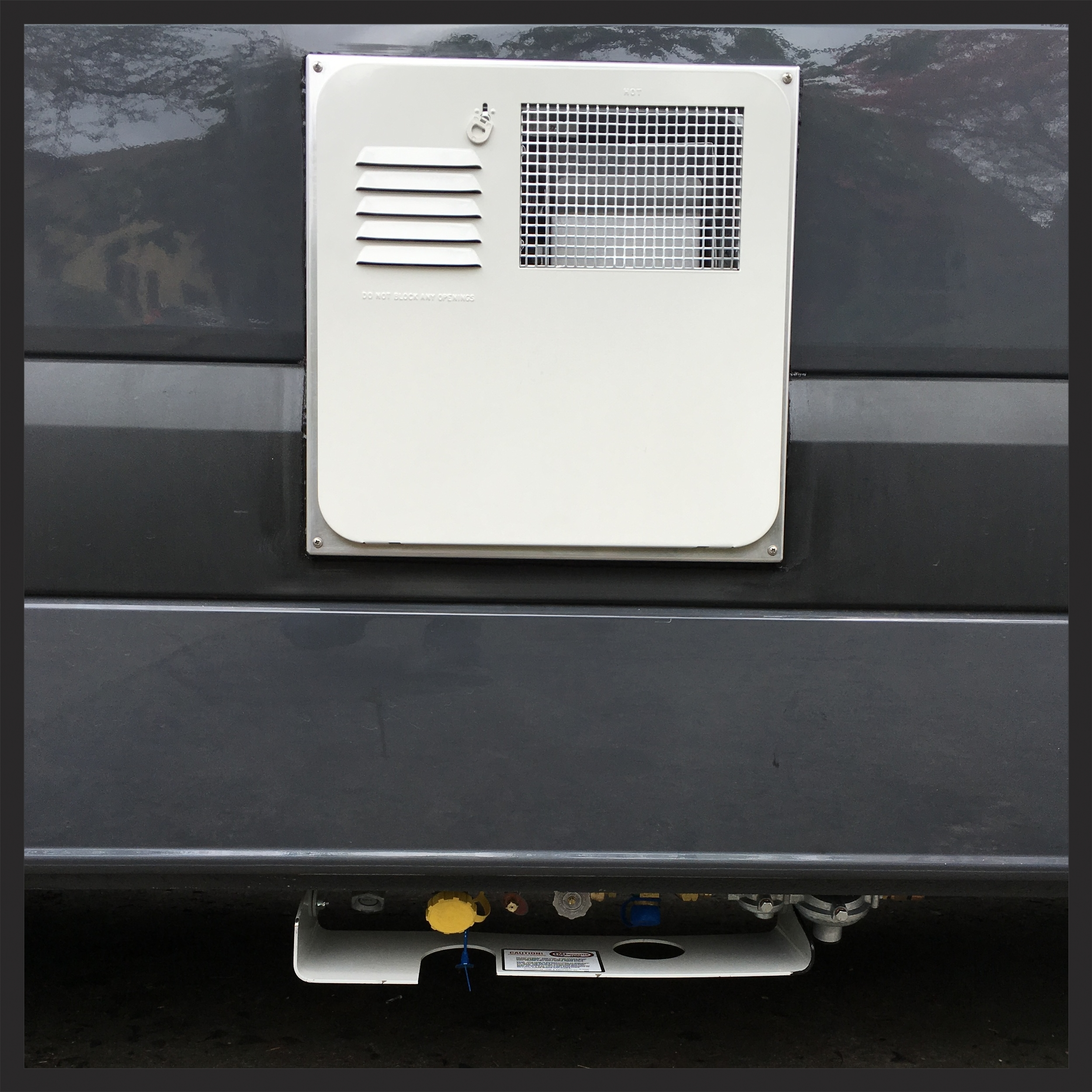The propane inlet and hot water and hot water heater grill