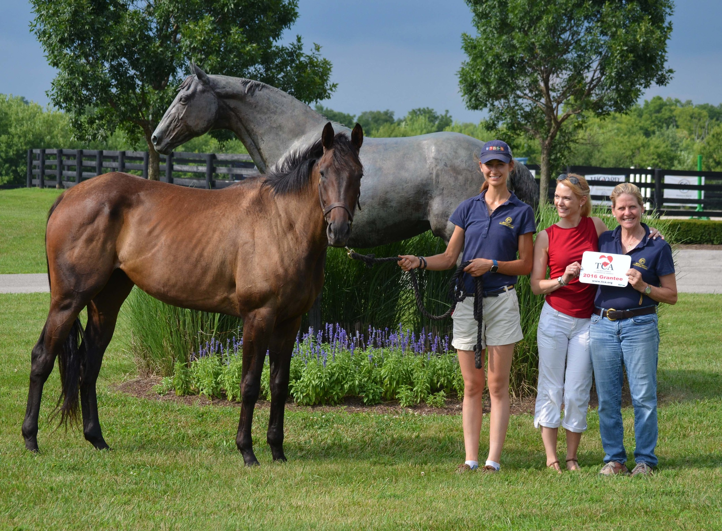 TCA Executive Director Erin Crady (middle) presents the grant award to MMSC Director Susanna Thomas (right) and MMSC Barn Manager/Trainer Erin Strader (left).