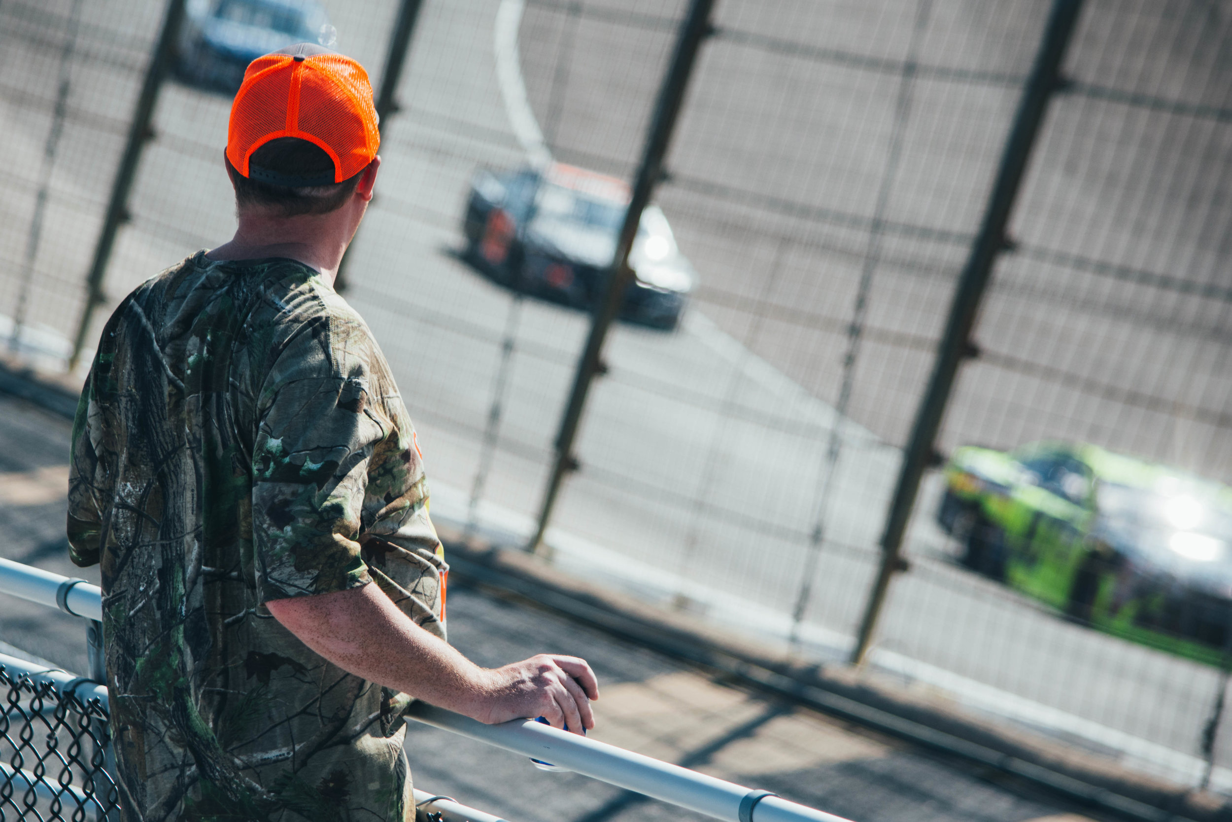 NASCAR fan watches as the cars race by for the first lap.