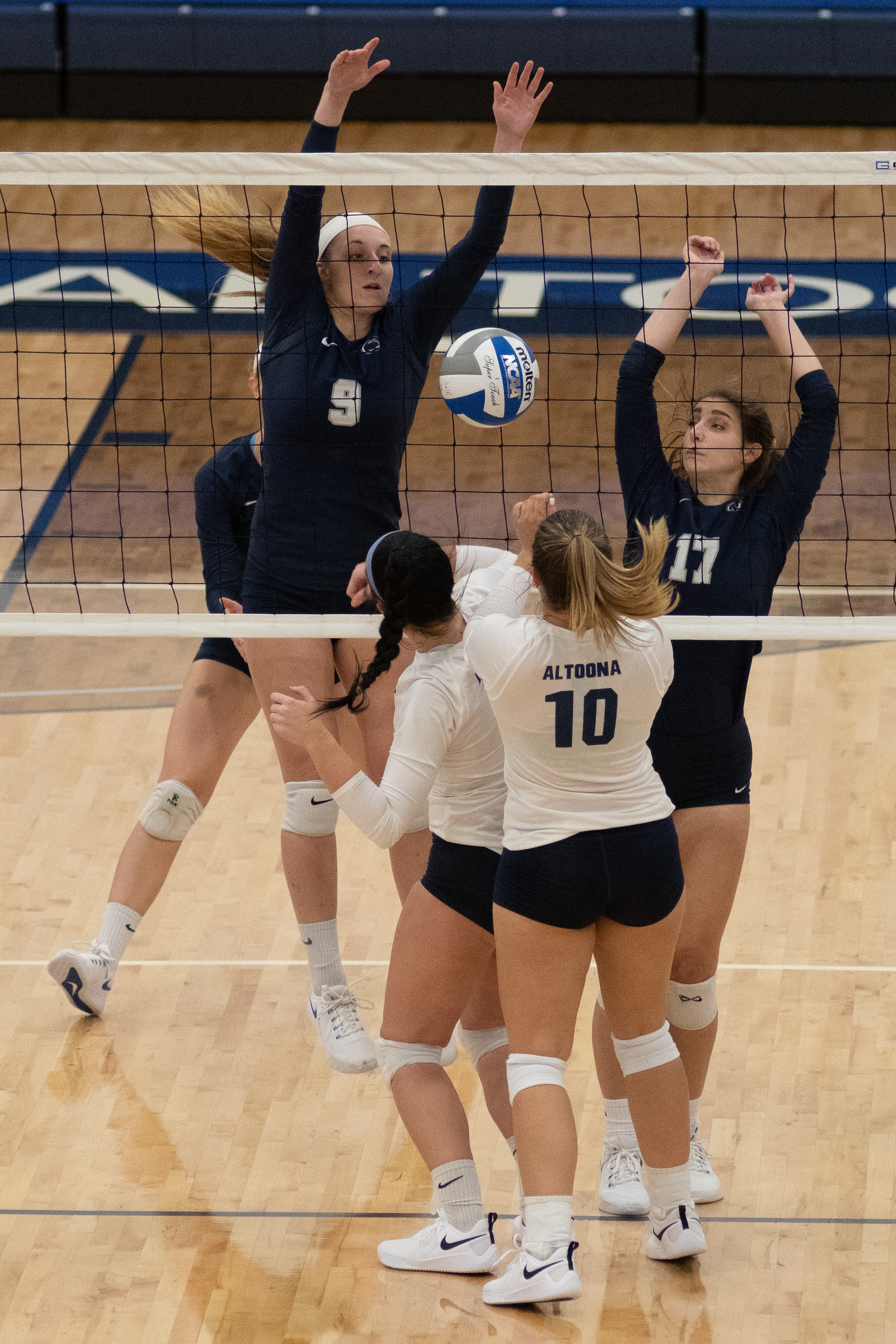 Penn State Harrisburg Women's Volleyball players Brittany Wolf (#9) and Erin Smallwood (#17) block the ball into Penn State Altoona players Paige Burk (#4) and Kelsey Bristol (#10) in their 3-0 win against Penn State Altoona.