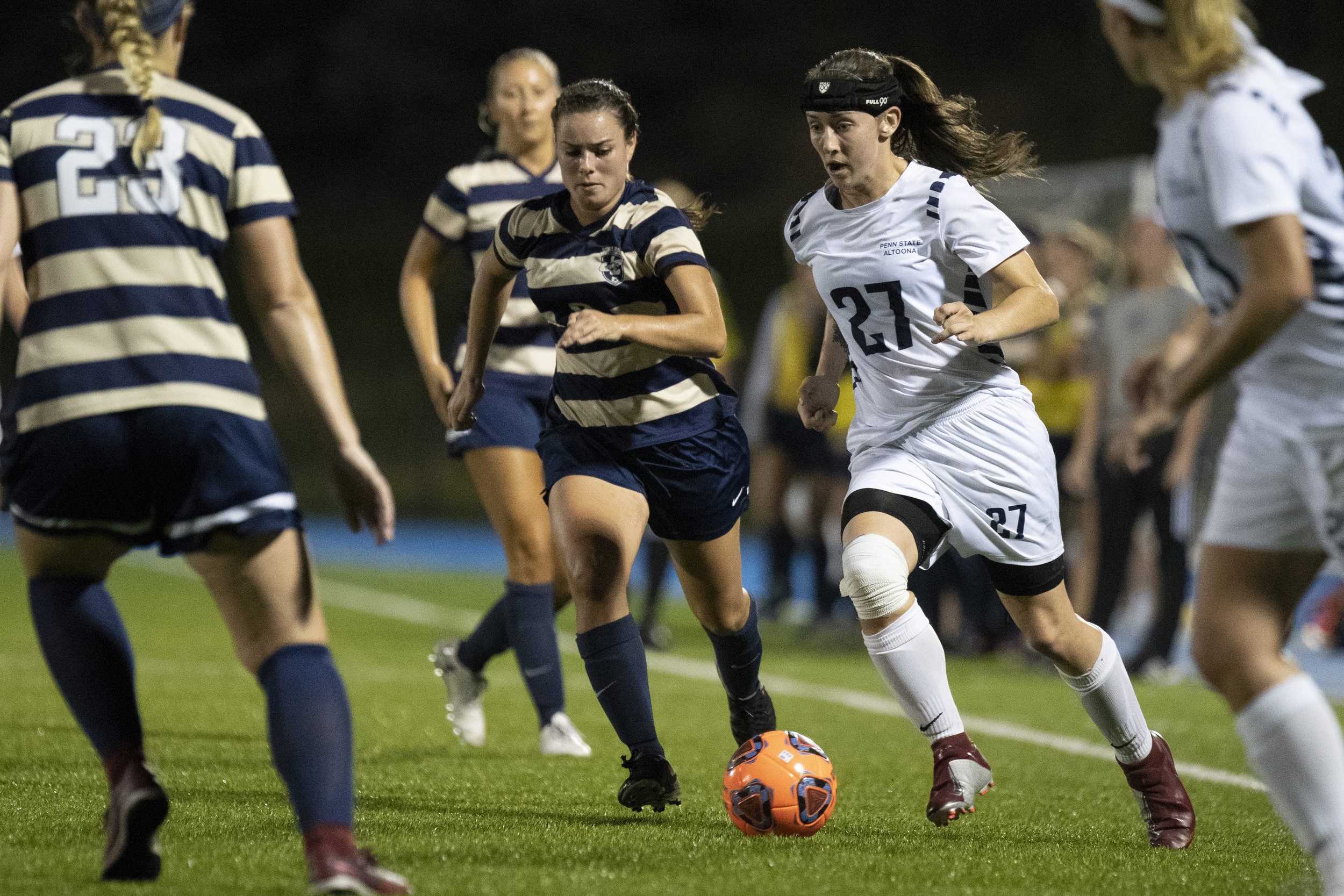 Penn State Altoona Women's Soccer player Kierra Irwin (#27) runs past Juniata College player Elizabeth Bentz (#6) and into Kristin Racis (#23) in Altoona's 4-1 win against Juniata College on Wednesday, September 19th, 2018 at Spring Run Stadium. - Photo By: Noah Riffe