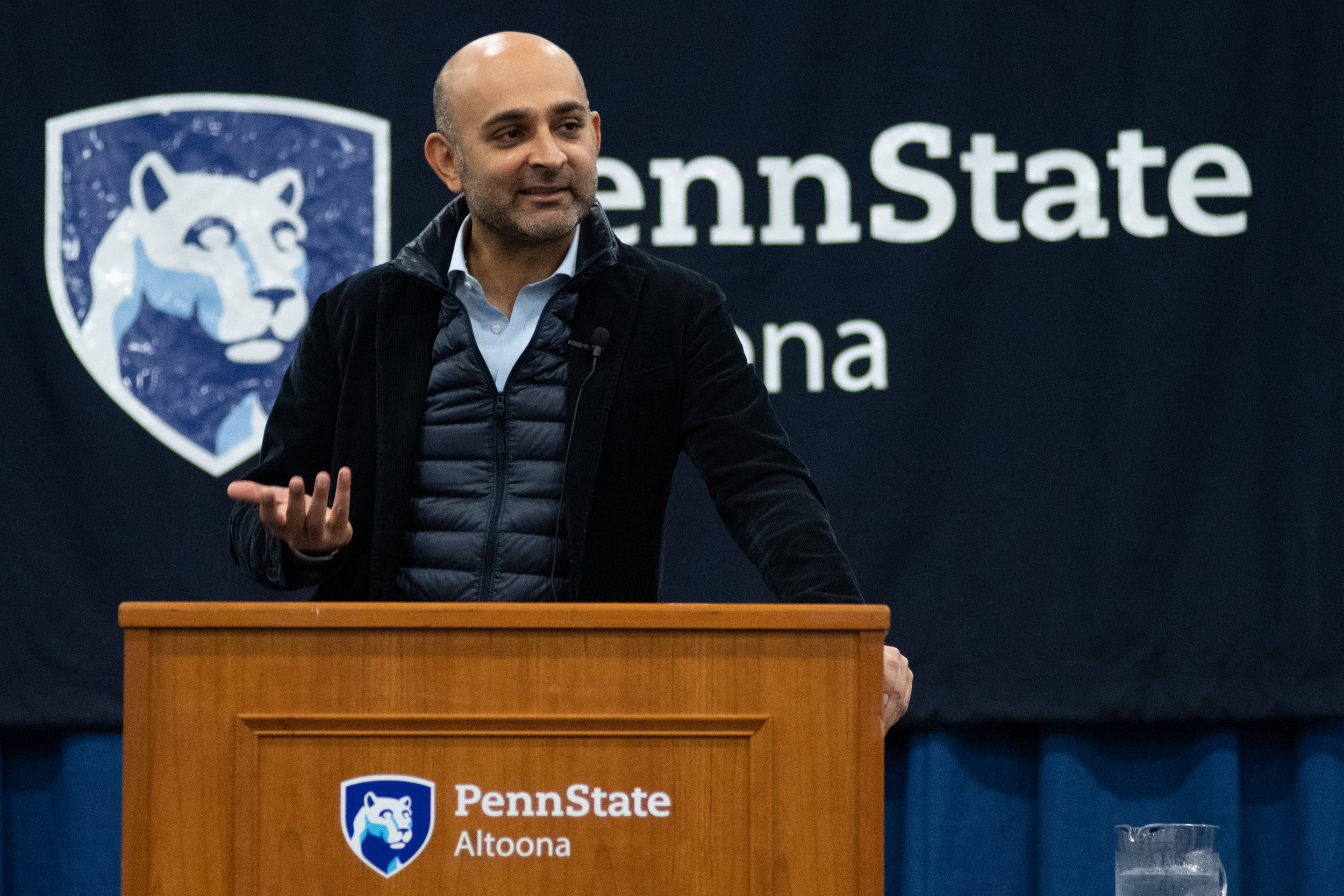 Photo by: Noah Riffe - Author Mohsin Hamid speaks on stage at Penn State Altoona's Adler Arena on September 25th, 2018. - Photo By: Noah Riffe