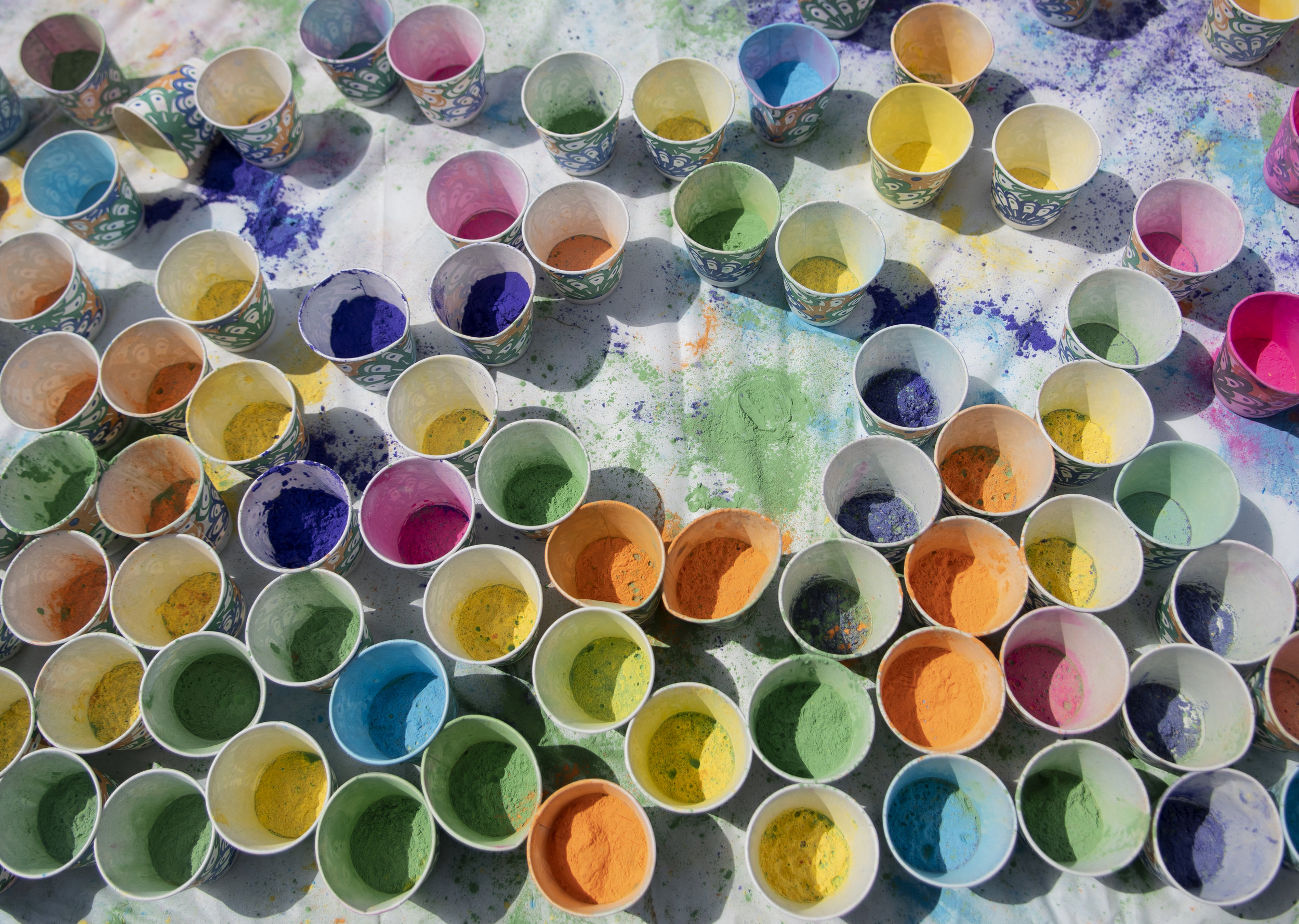 Cups of colored powder cover a table during the Hindu festival, Holi, hosted by the Indian Culture and Language Club and South Asian Student Association on Sunday, April 7, 2019 at the HUB-Robeson Center lawn. | Photo by: Noah Riffe