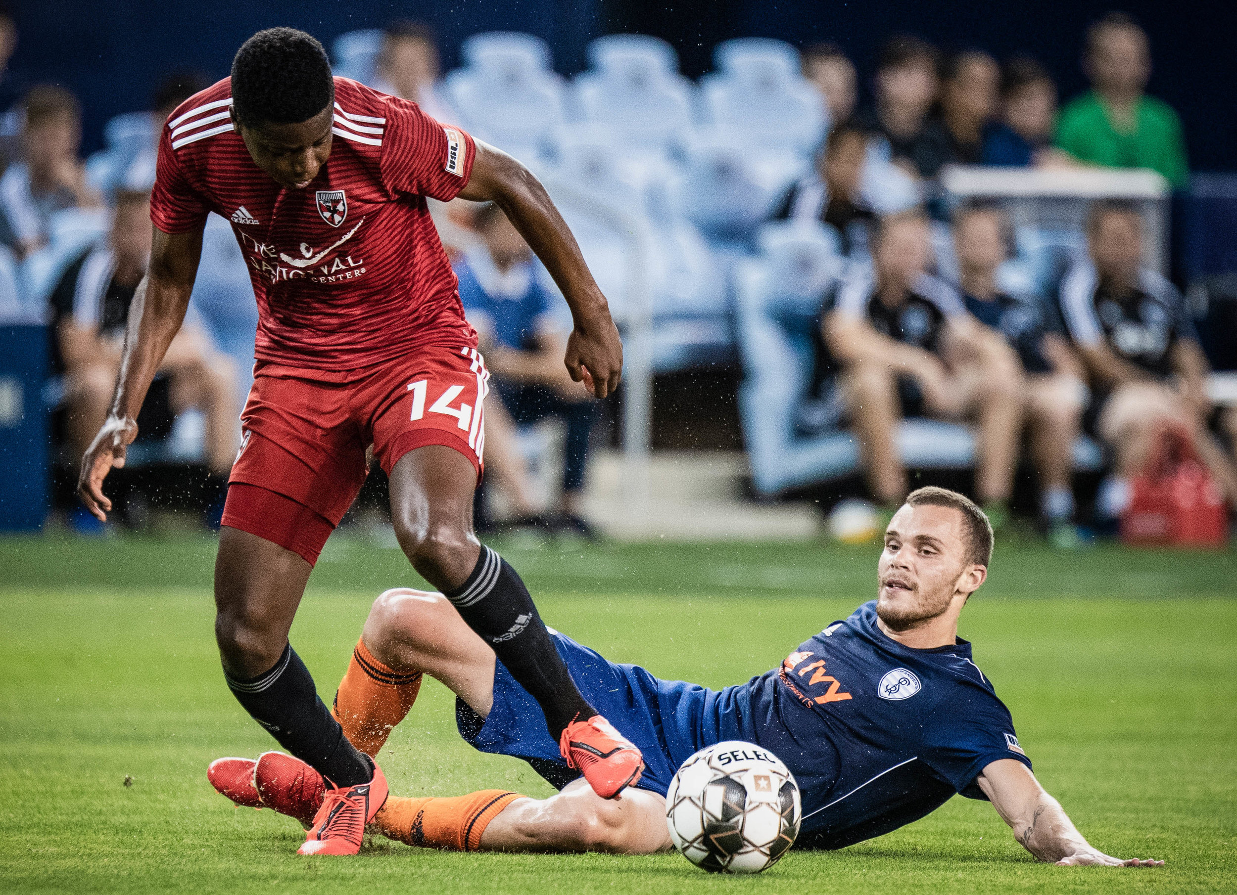 Forward, Ethan Vanacore-Decker gets tripped by Bryang Kayo (14) during the Swope Park Rangers vs. Loudoun United FC match on Wednesday, June 5, 2019 at Children's Mercy Park, Kansas City, Kansas. | Photo by: Noah Riffe