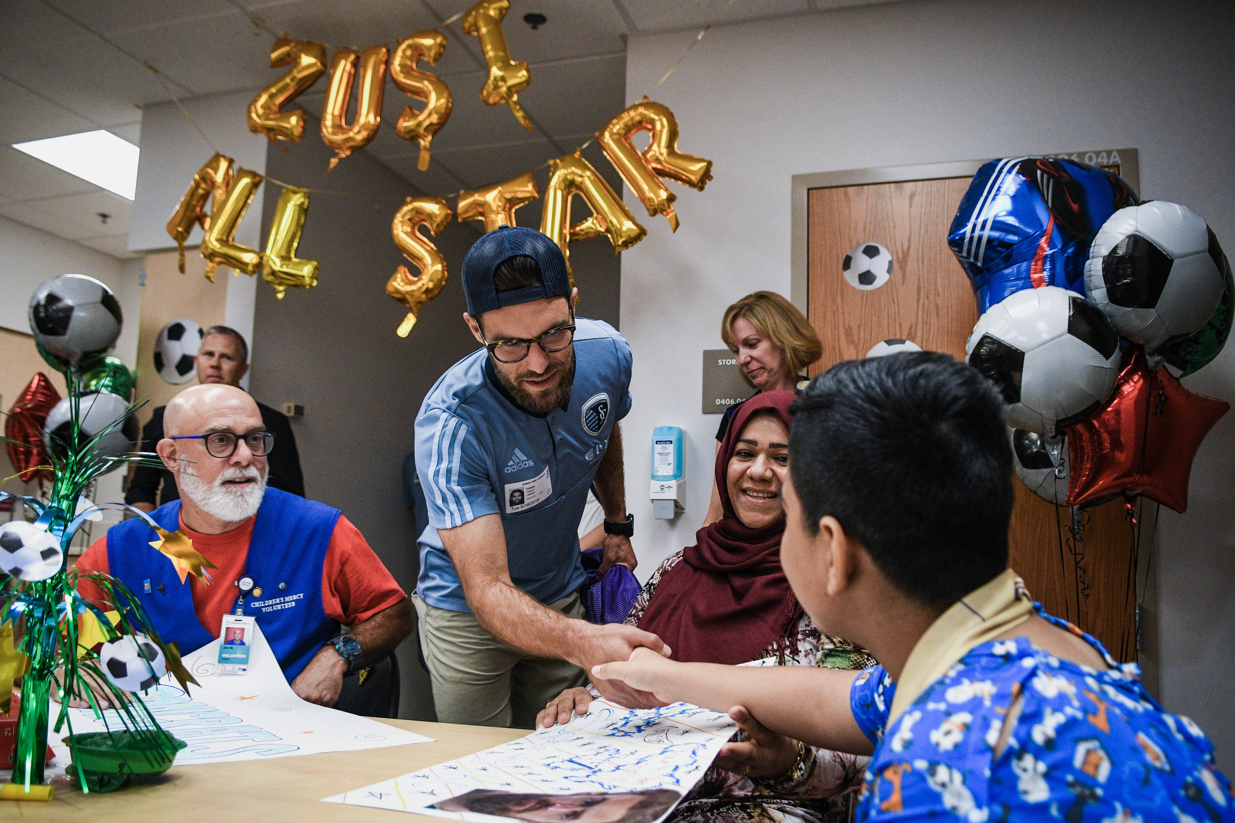 Sporting Kansas City defender Graham Zusi shakes hands with a patient after he was surprised at Children's Mercy Hospital in Kansas City with the news he was voted on to the 2019 Major League Soccer All-Star team. This will be Zusi's 7th appearance on the all-star roster.