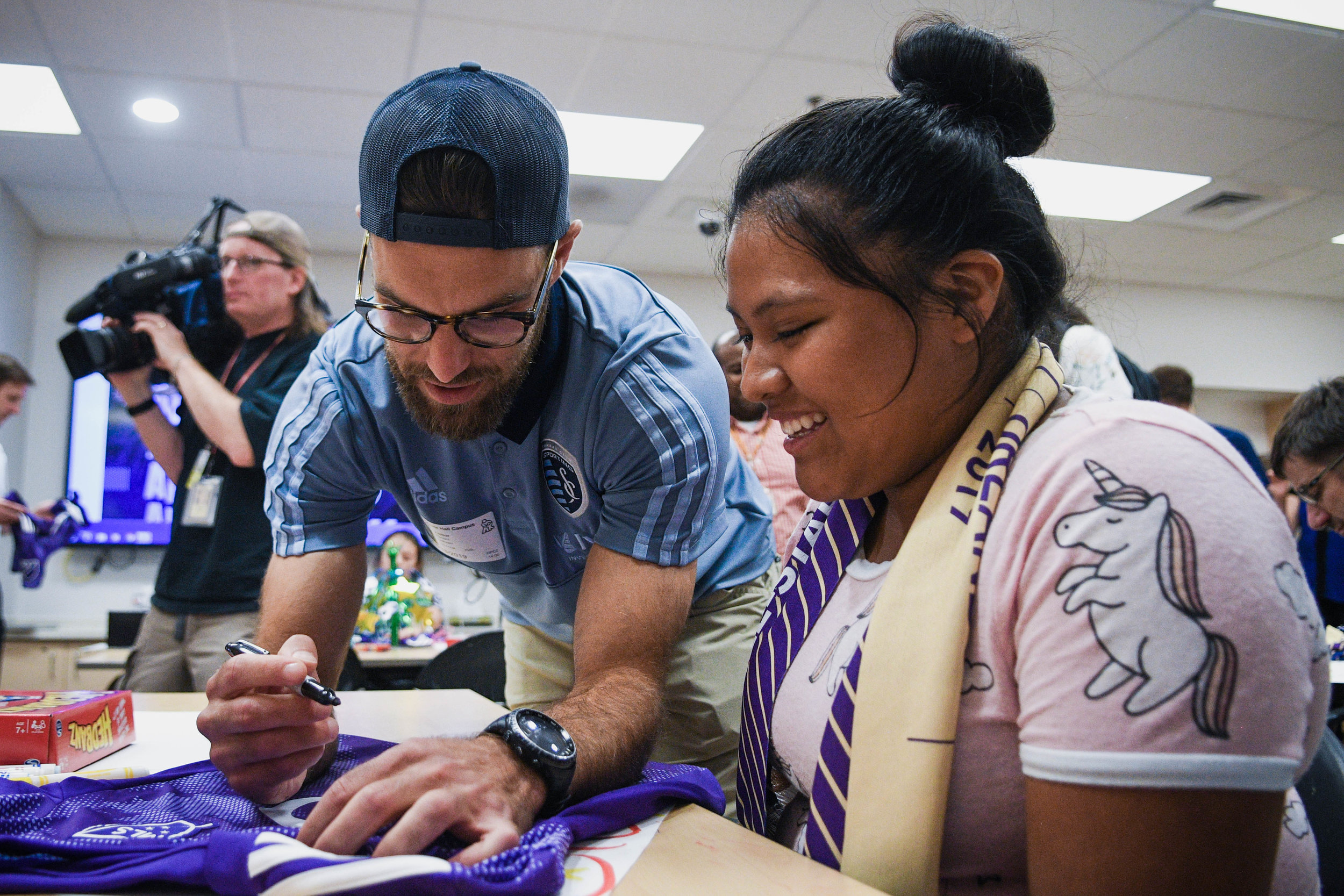 Sporting Kansas City defender Graham Zusi signs a jersey for a patient after he was surprised at Children's Mercy Hospital in Kansas City with the news he was voted on to the 2019 Major League Soccer All-Star team. This will be Zusi's 7th appearance on the all-star roster.