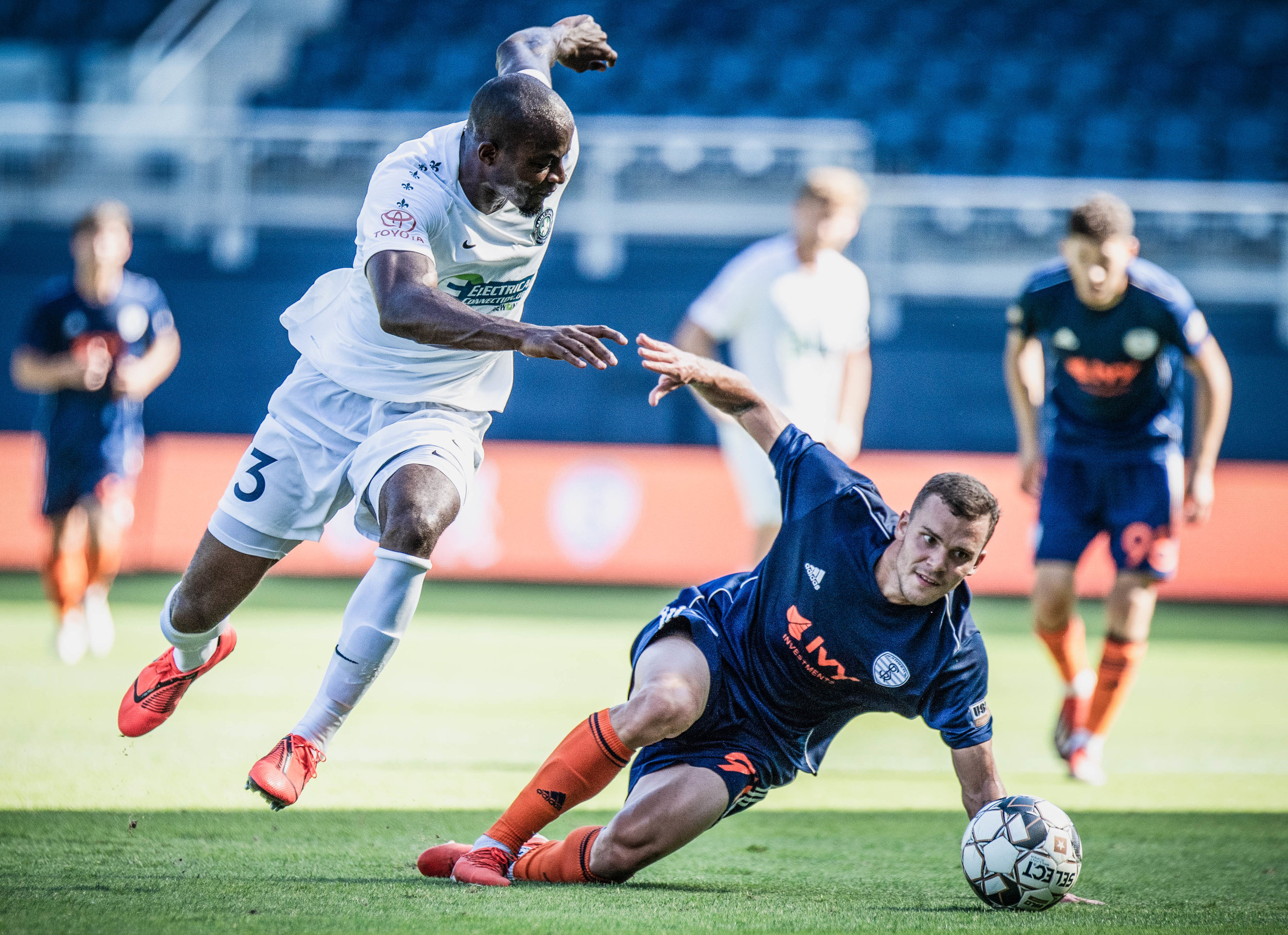 Ethan Vanacore-Decker (91) is tripped up by Phanuel Kavita (3) during the Swope Park Rangers vs. Saint Louis FC match on Sunday, June 30, 2019 at Children's Mercy Park in Kansas City, Kansas. The Rangers took down Saint Louis 2-1 breaking their 8 game winless streak.