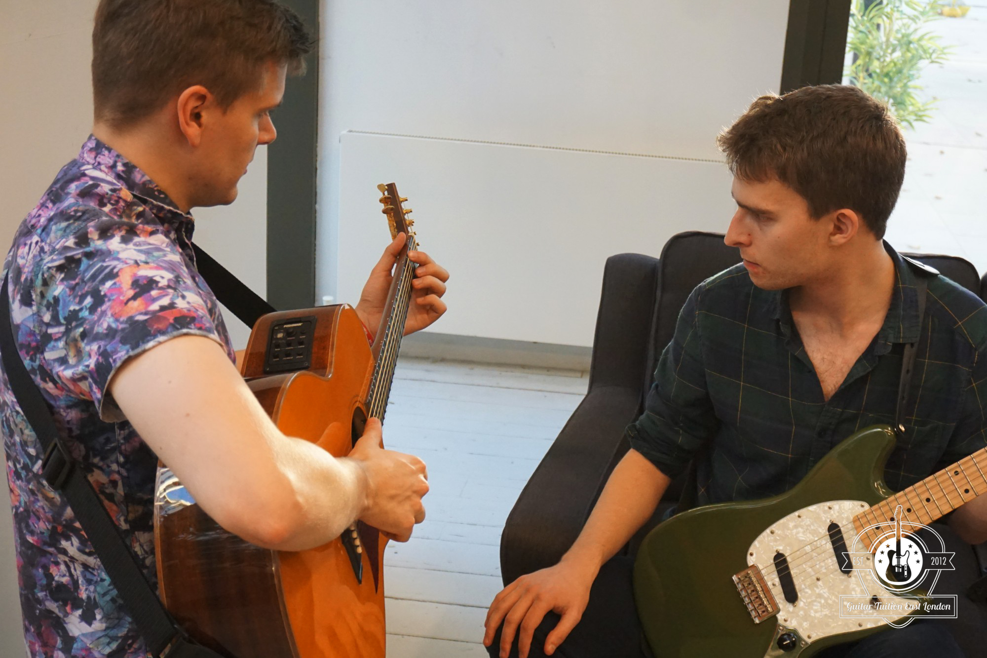 One of our teachers, Darryl with Rob, our student working on fingerpicking.