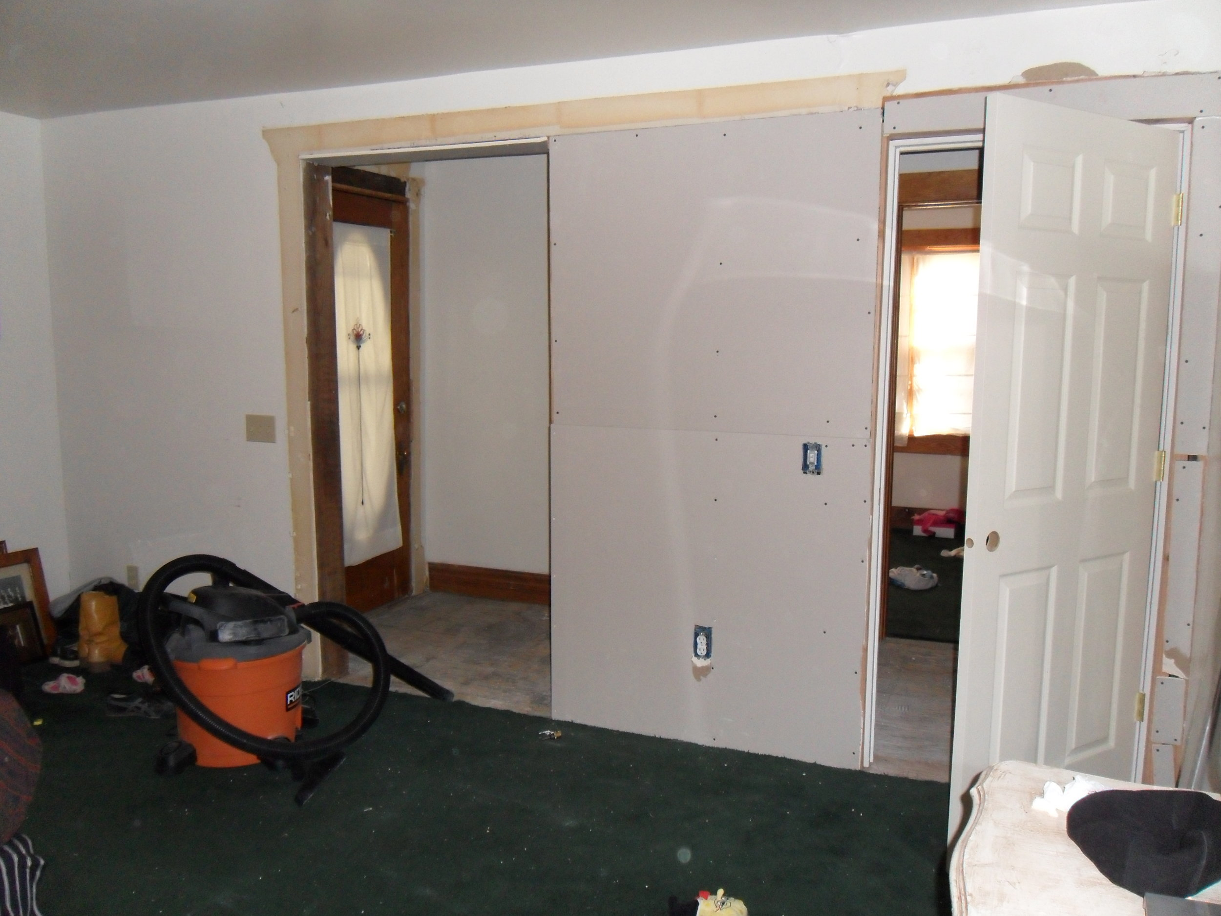 Archway framed in for a closet and new bedroom door. Notice the front door is still in place.