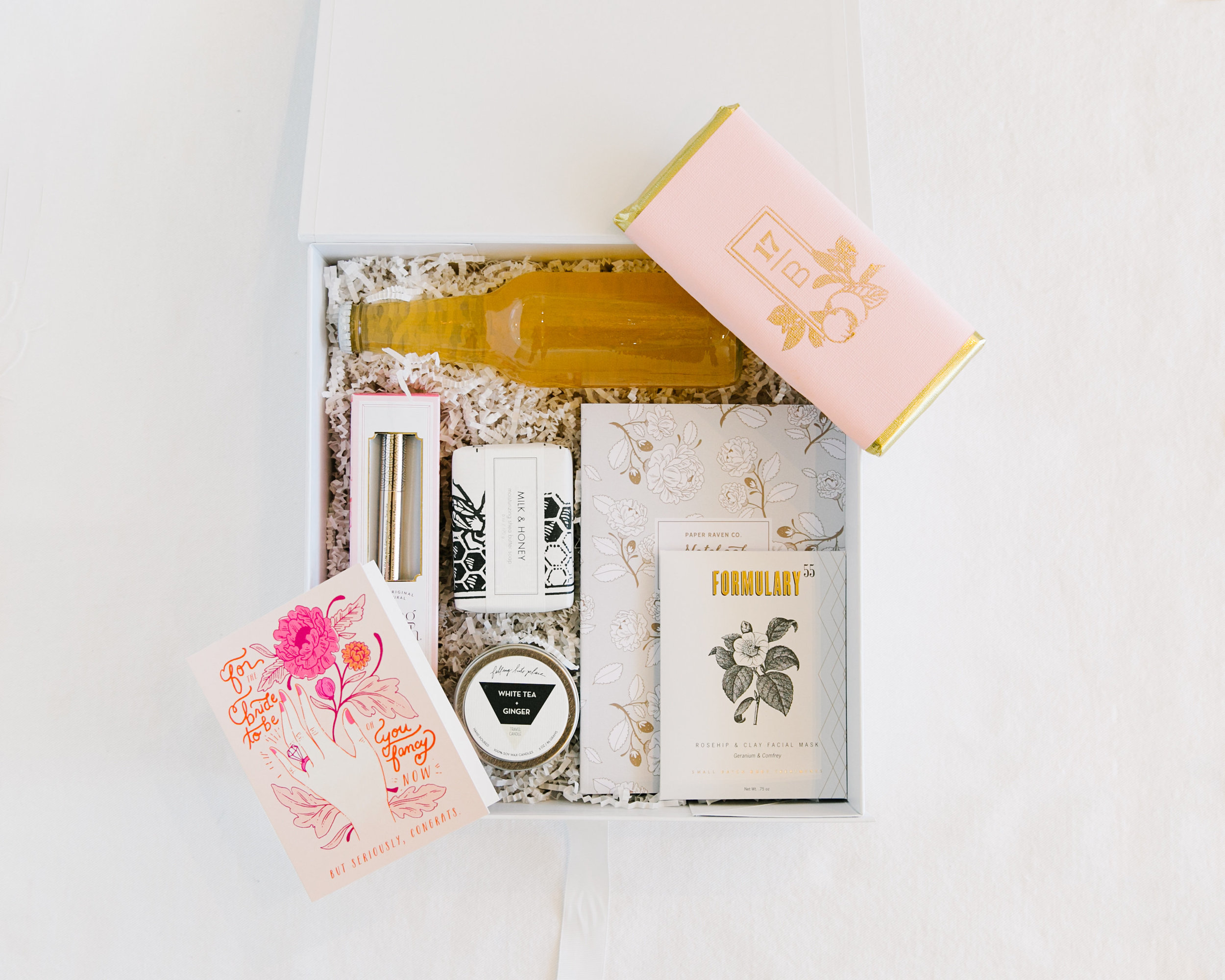 """HAPPILY EVER AFTER""  :  a premium keepsake box, perfect for a bride-to-be to commemorate her groom popping the question.  Includes a congratulations card, a bubbly beverage, a notebook for wedding ideas, a Bling Brush to shine her ring, chocolate bar, + all the relaxation essentials : face mask, bath fizzy, + candle."