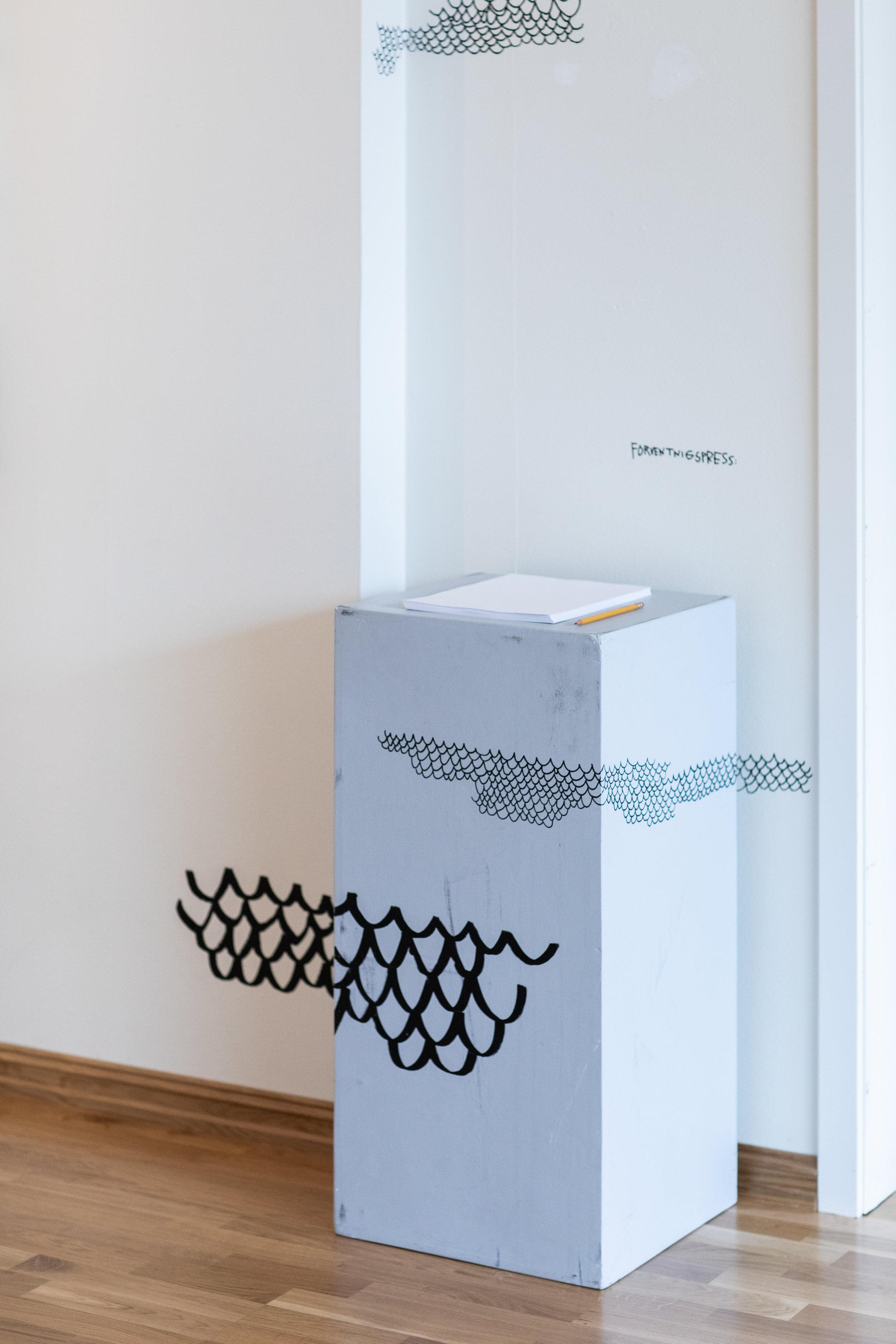 """Installasjonen """"Forventingspress"""": en bunke blanke ark og en blyant med påskriften """"Hva som helst""""."""