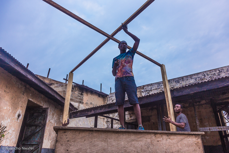 A carpenter works on a performance art structure on the eve of the Chale Wote Street Art Festival. Accra, 2017.