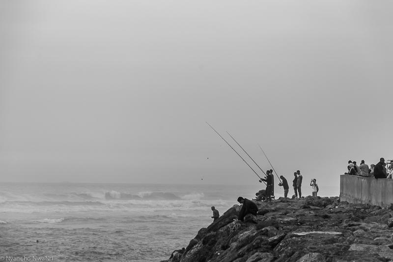 Young men fishing at the beach. Casablanca, Morocco. 2017