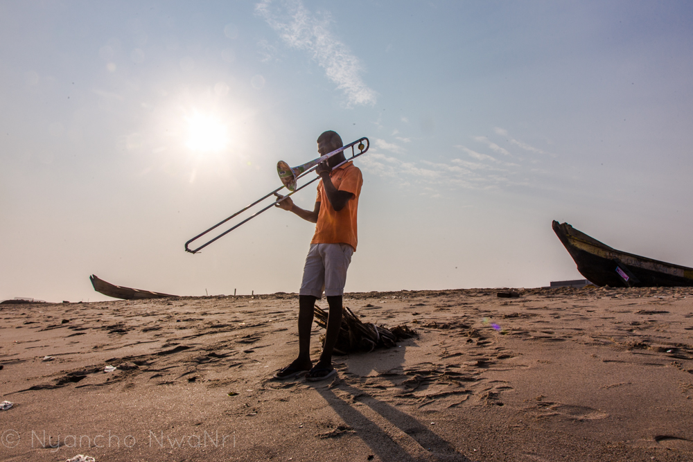 A young musician practices with his trombone on the beach. Accra, Ghana. 2017