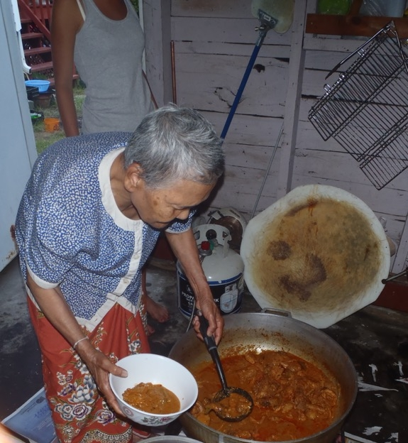 Makara's mother serving a bowl of her Cambodian curry stew