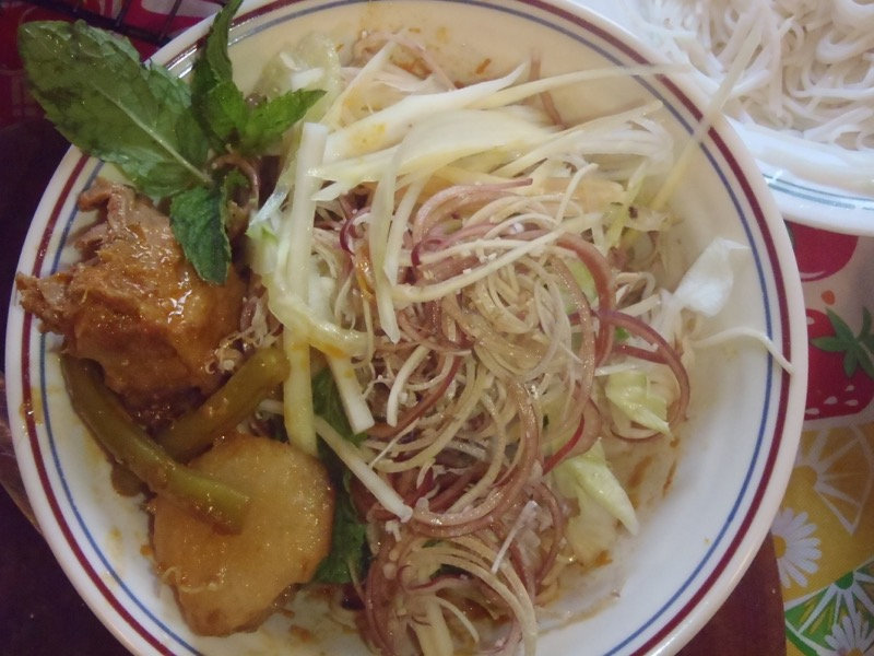 The stew is topped with fresh mung bean sprouts, mint and shaved banana flower.