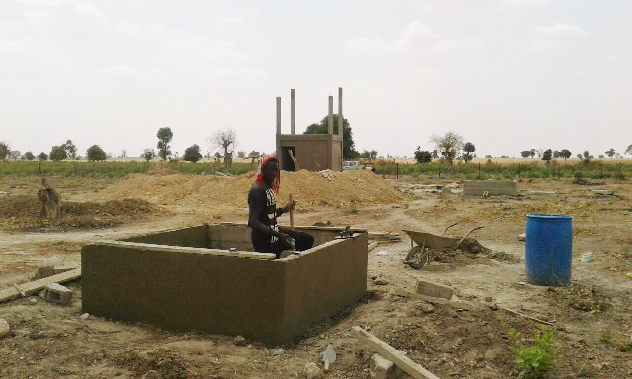 Construction underway at Daga Sambou Market Garden - water distribution system in foreground, water pump and tank structure in background.