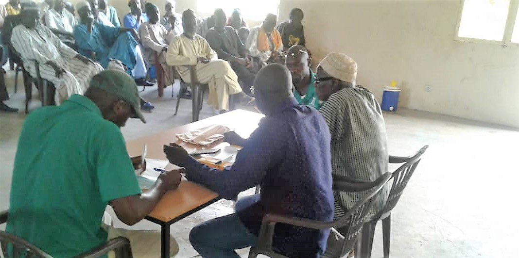 Andando staff, Camara (pictured left), recording the loan distribution amounts and repayments.