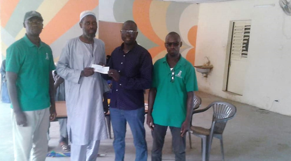 Andando staff Camara (left) and Mandaw (right) along with the mayor of Keur Soce distributing funds to this year's loan recipients.