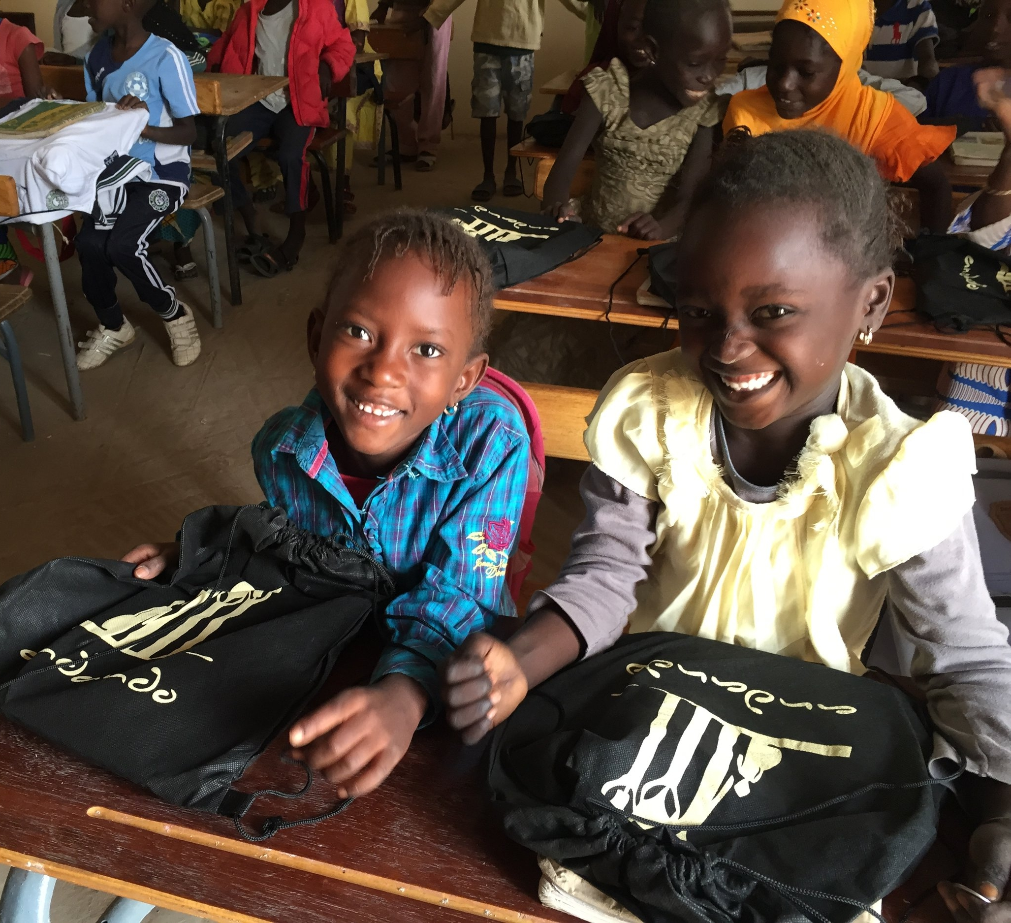 Happy students receiving new supplies at one of our partner schools.