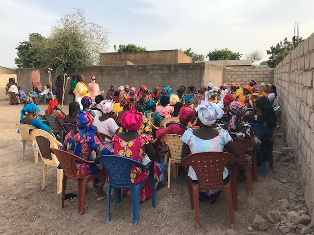 Women fill the courtyard near a health post, excited to learn how they can better improve the health of their families and communities.